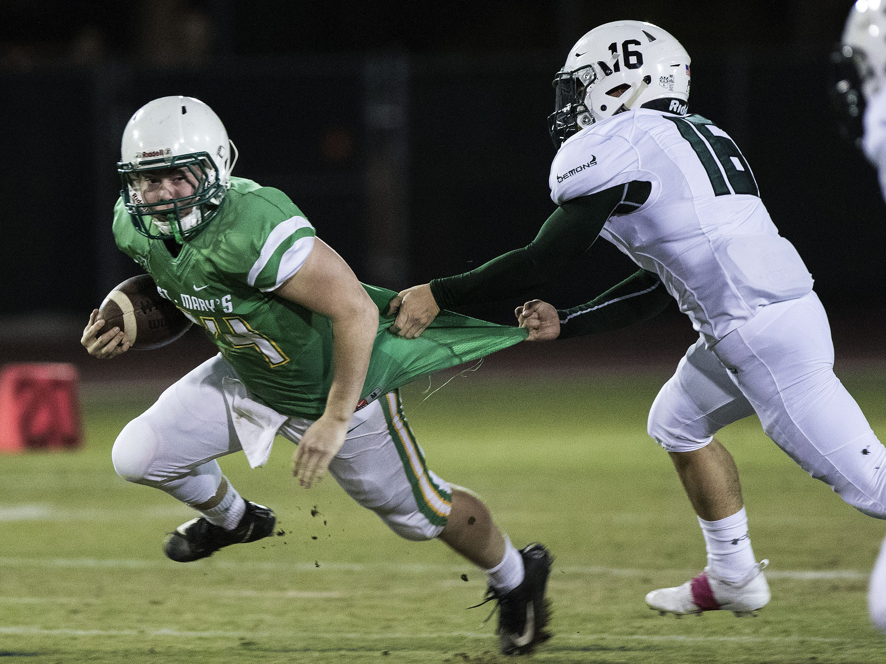 St. Mary's Jack Flanagan has his jersey pulled as Greenway's Jace Creed makes a tackle during their game at Phoenix College in Phoenix Friday, Oct. 12, 2018. #azhsfb
