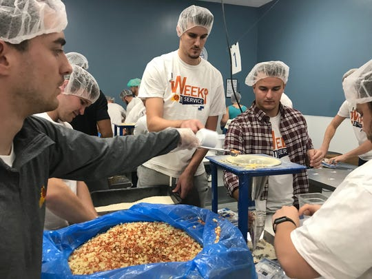 Phoenix Suns center Dragan Bender serving at Feed My Starving Children Friday evening