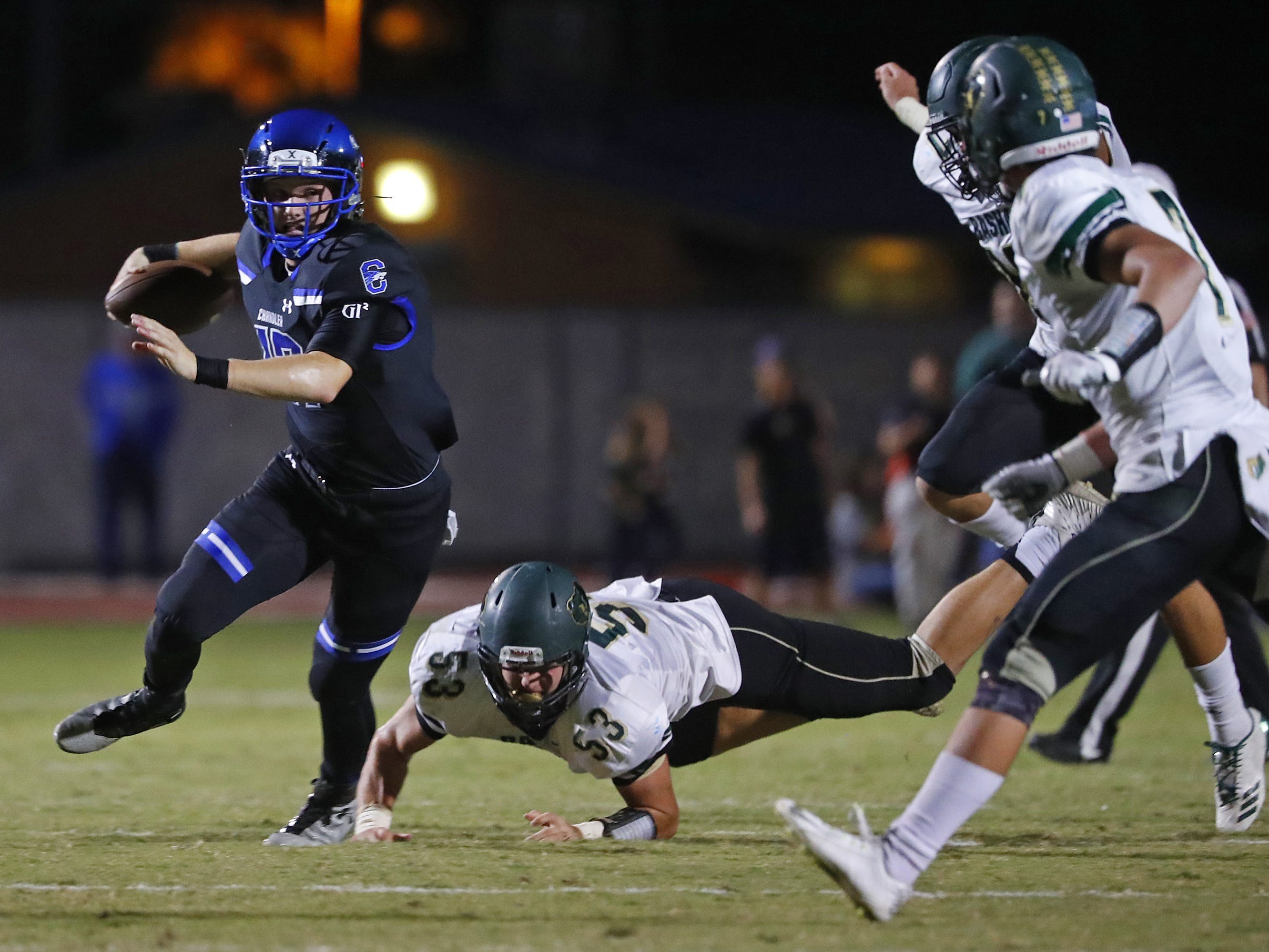Chandler's Jacob Conover (17) scrambles from Basha's 	Sean Smeltzer (53) at Chandler High School in Chandler, Ariz. on October 12, 2018.