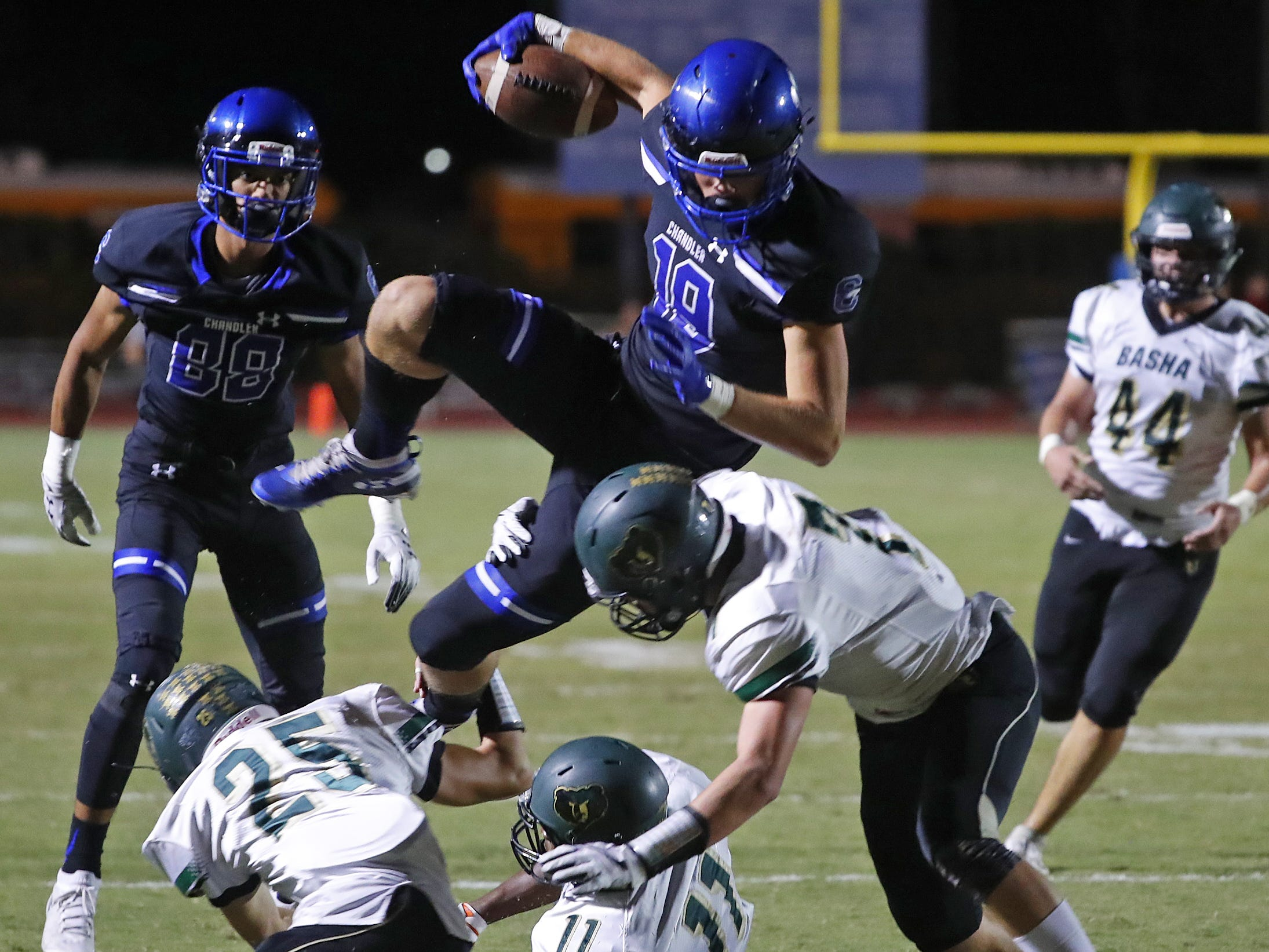 Chandler's Brayden Liebrock (19) hurdles a tackle from Basha's Nicholas Schinker (7) at Chandler High School in Chandler, Ariz. on October 12, 2018.