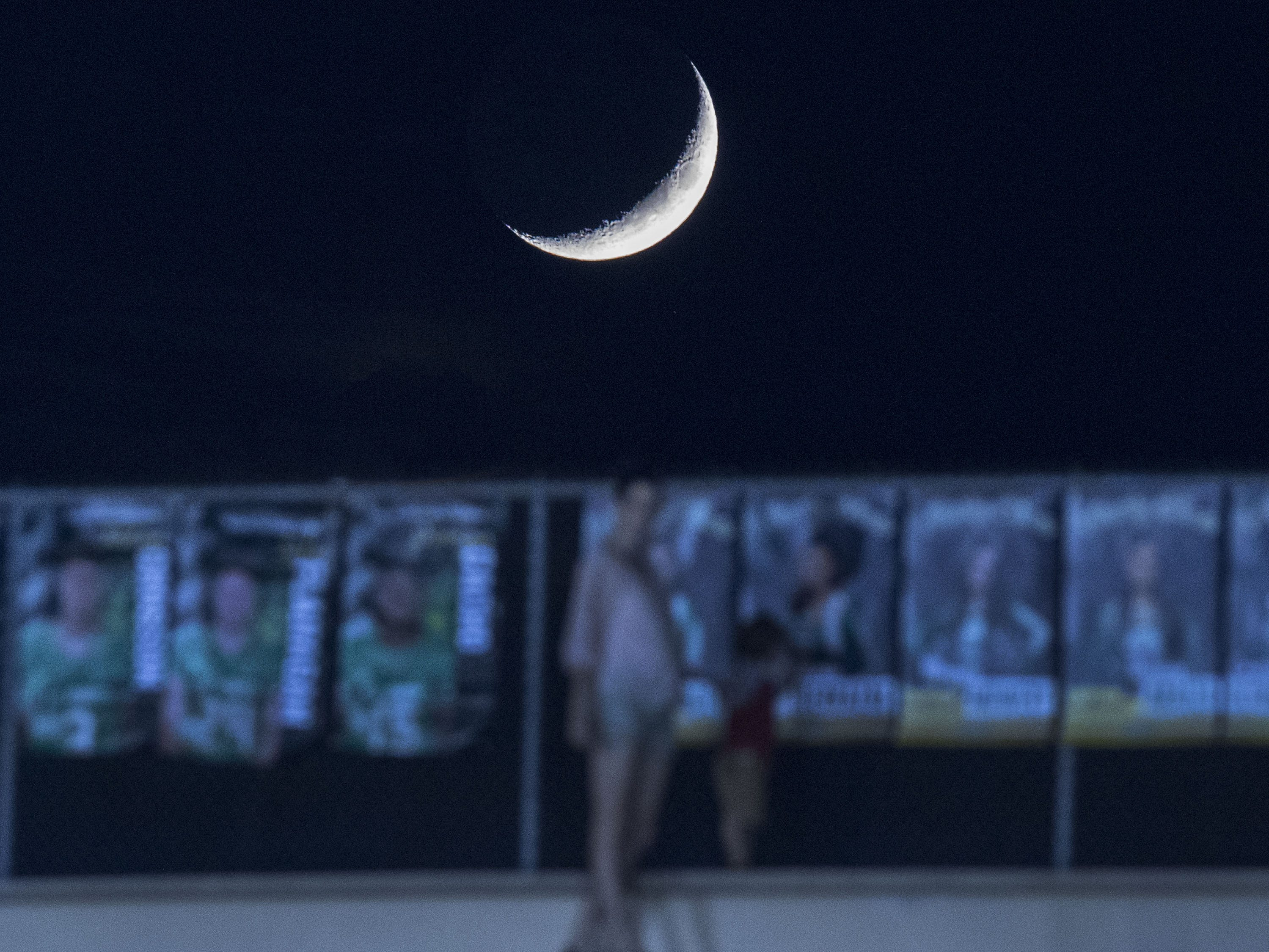 A mother watches her child at the top of Hoy Stadium as a sliver of the moon sets during the St. Mary's-Greenway game at Phoenix College in Phoenix Friday, Oct. 12, 2018. #azhsfb