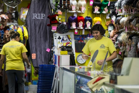 Michael Hernandez works behind the wig counter at Easley's Fun Shop on Thursday, Oct. 11, 2018, in Phoenix. The costume and gag store is closing at the end of the year after operating for 72 years.