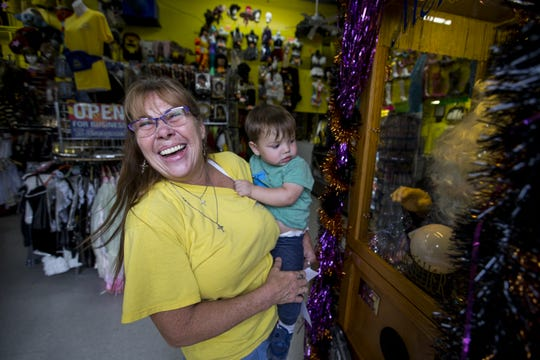 Debbie Easley plays with her nephew, London Dominguez, at Easley's Fun Shop on Thursday, Oct. 11, 2018, in Phoenix. The costume and gag store is closing at the end of the year after operating for 72 years.