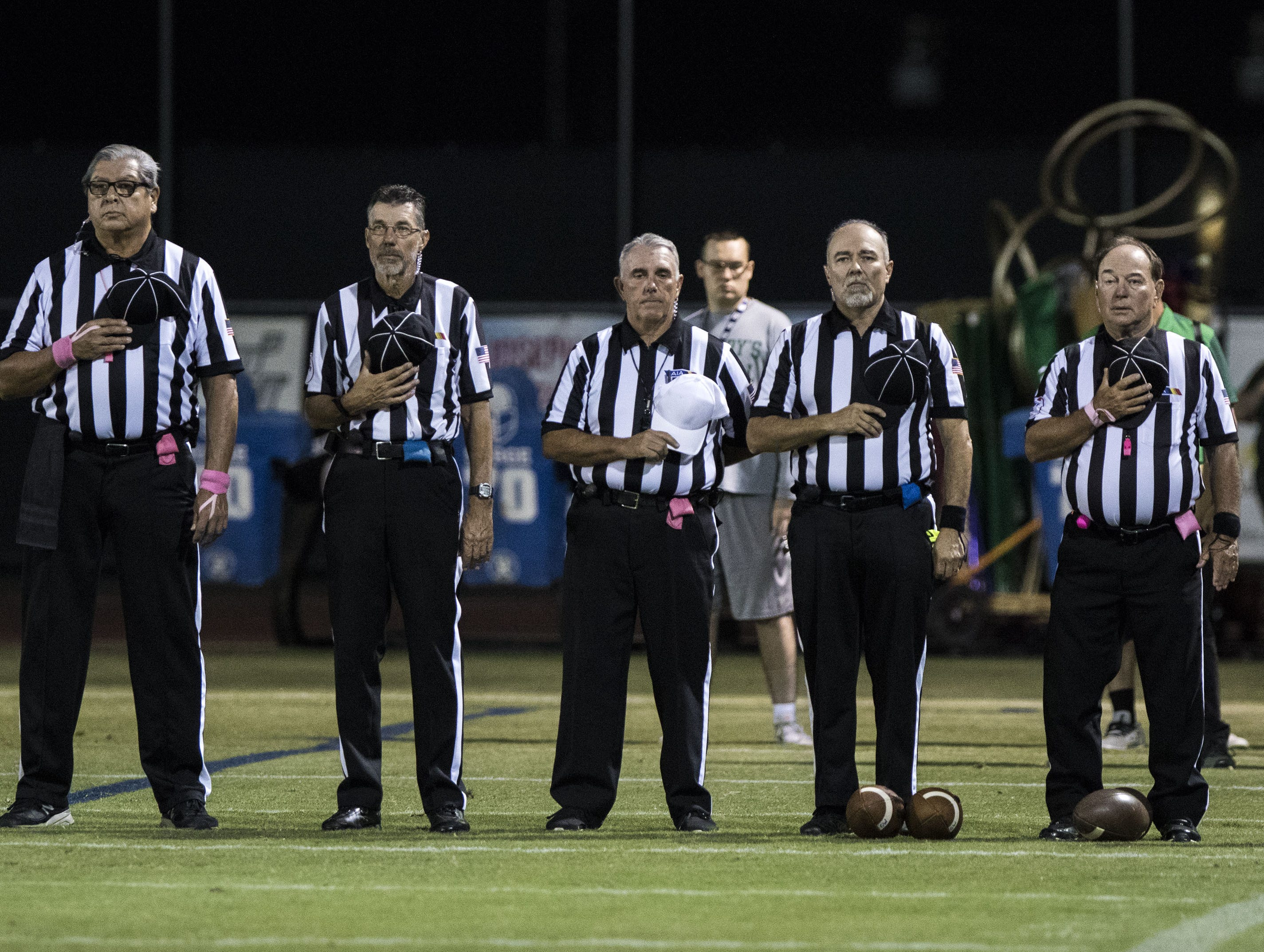 High School football officials stand during the National Anthem before their game with Greenway and St. Mary's at Phoenix College in Phoenix Friday, Oct. 12, 2018. #azhsfb