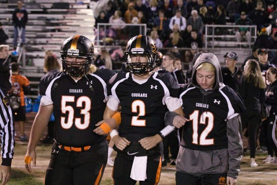 Palmyra seniors, from left, John Pallone, Grant Haus and Kyle Wasilewski head out for the coin toss prior to Friday's Senior Night clash with Milton Hershey. The Cougars endured their first loss, falling 28-14.