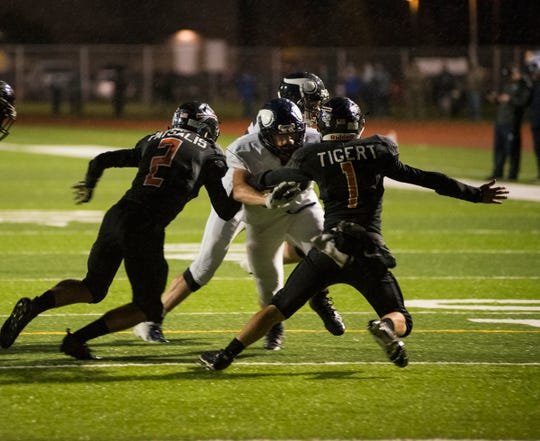 Marysville High School's Hunter Delor pushes through Marine City High School's Charles Tigert (1) and Angelo Patsalis (2) during their game Friday, Oct. 12, 2018 at East China Stadium. Delor continued running to get Maryville's first touchdown.