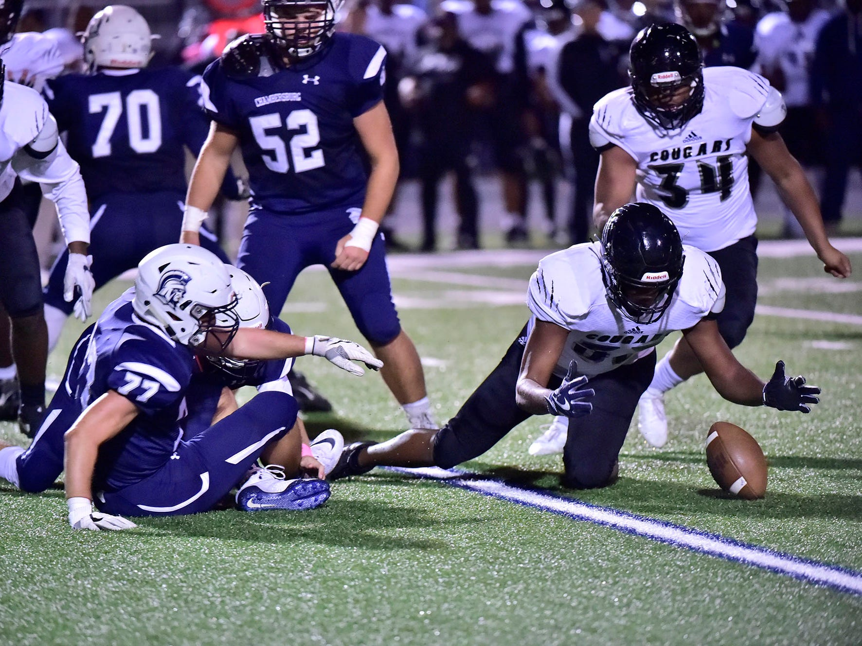 Harrisburg's Tony Patterson, right,  recovers a fumble. Chambersburg dropped a 28-13 game against Harrisburg in PIAA football on Friday, Oct. 12, 2018.