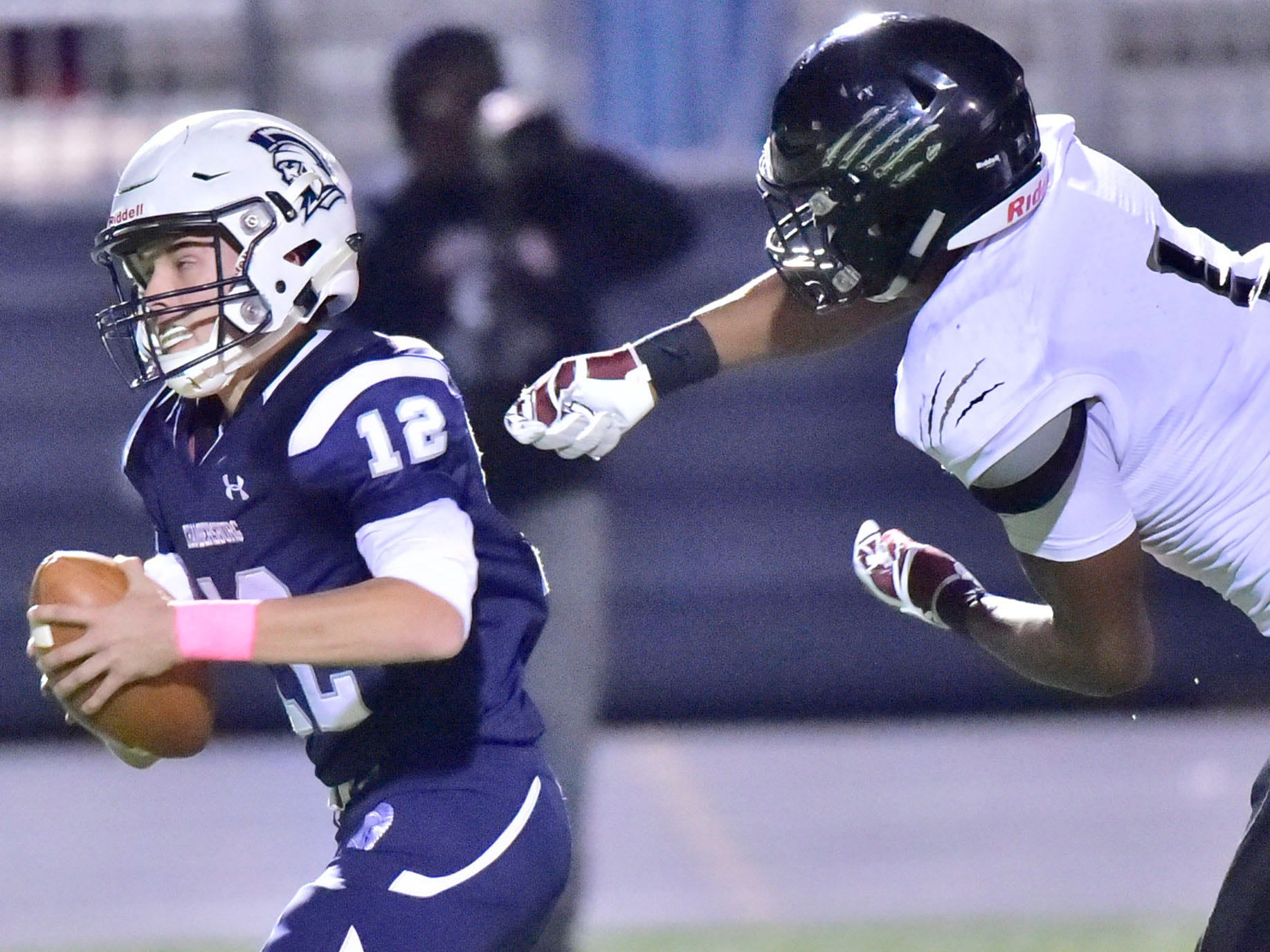 Chambersburg's QB Brady Stumbaugh (12) scrambles away from a Harrisburg defender. Chambersburg dropped a 28-13 game against Harrisburg in PIAA football on Friday, Oct. 12, 2018.
