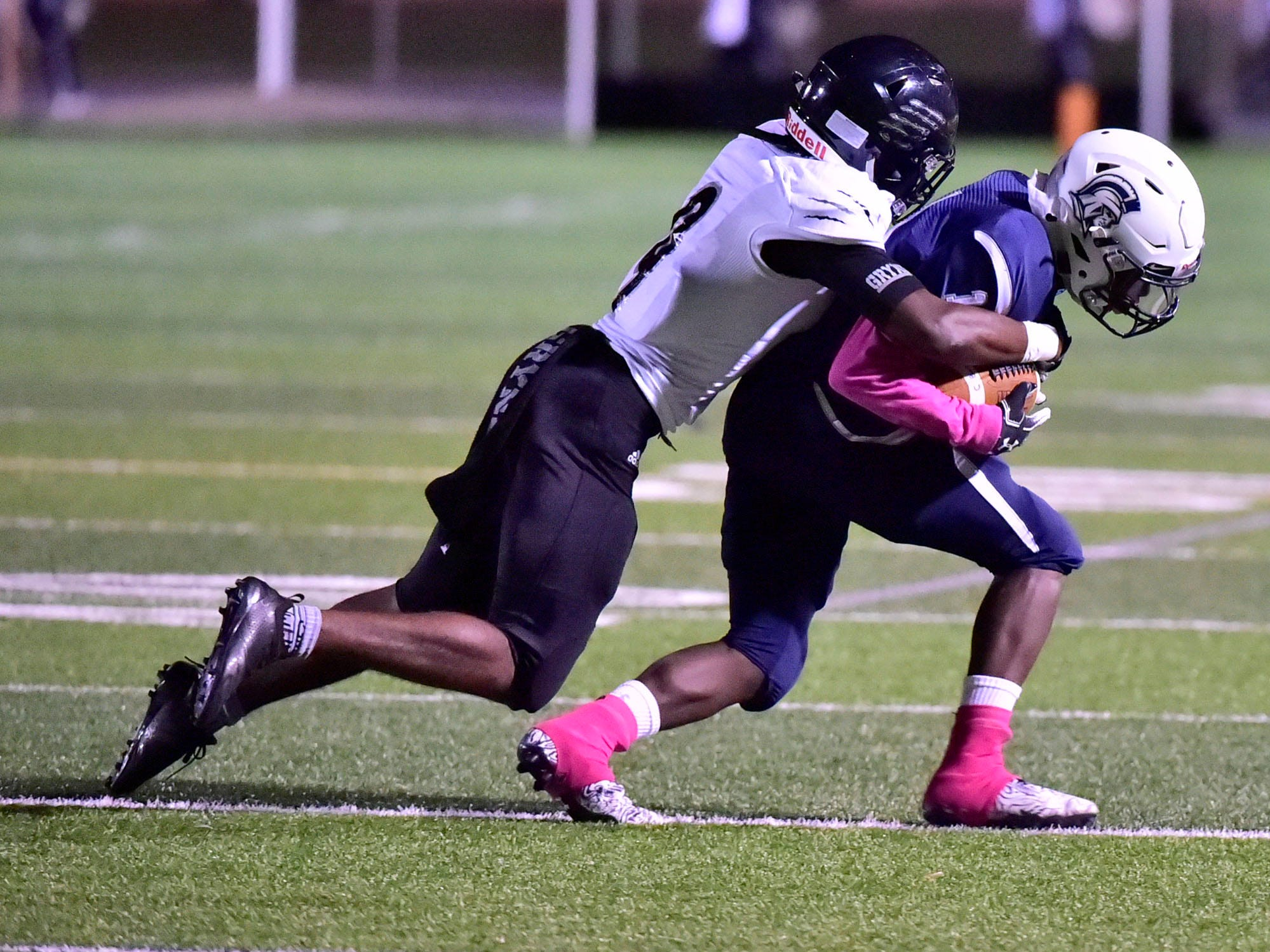 Chambersburg's Kevin Lee, right, runs away from Harrisburg's Donte Kent after catching a pass. Chambersburg dropped a 28-13 game against Harrisburg in PIAA football on Friday, Oct. 12, 2018.