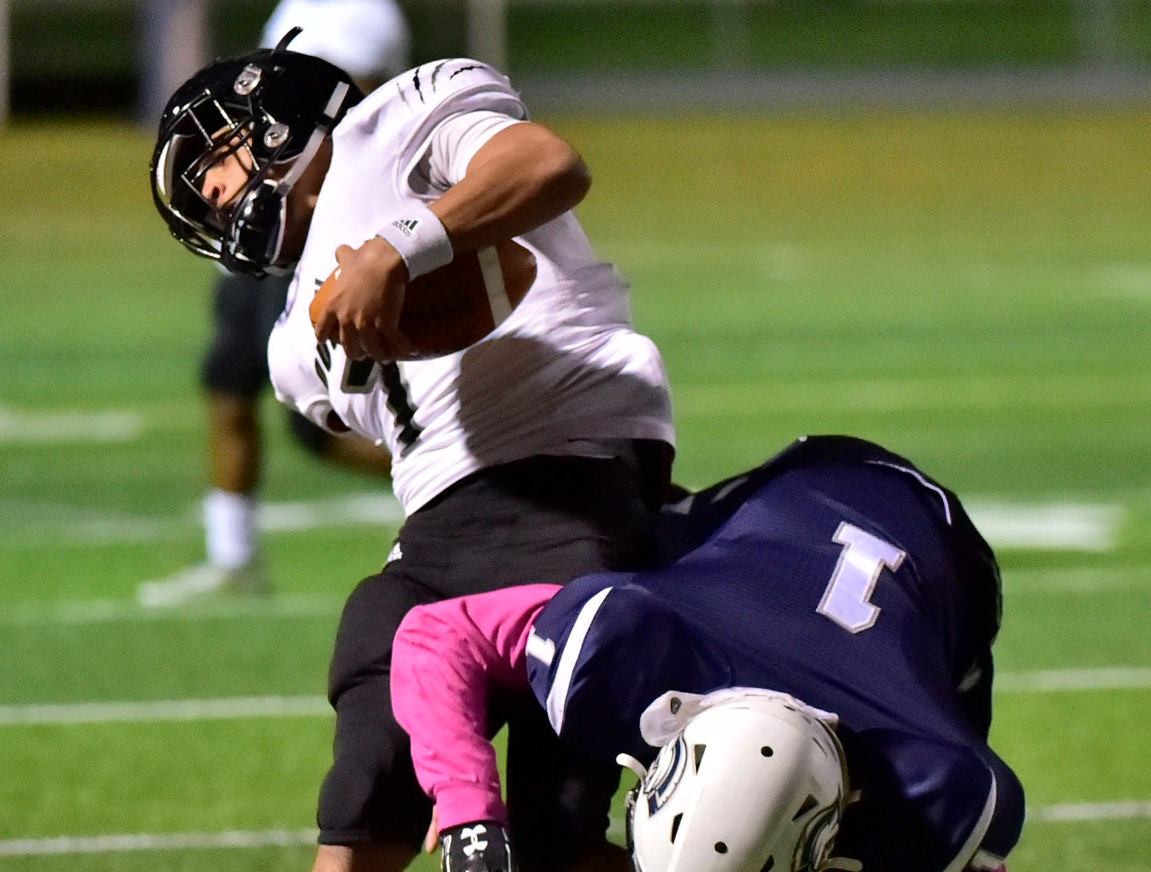 Chambersburg's Kevin Lee (1) hits Harrisburg QB Kane Everson. Chambersburg dropped a 28-13 game against Harrisburg in PIAA football on Friday, Oct. 12, 2018.