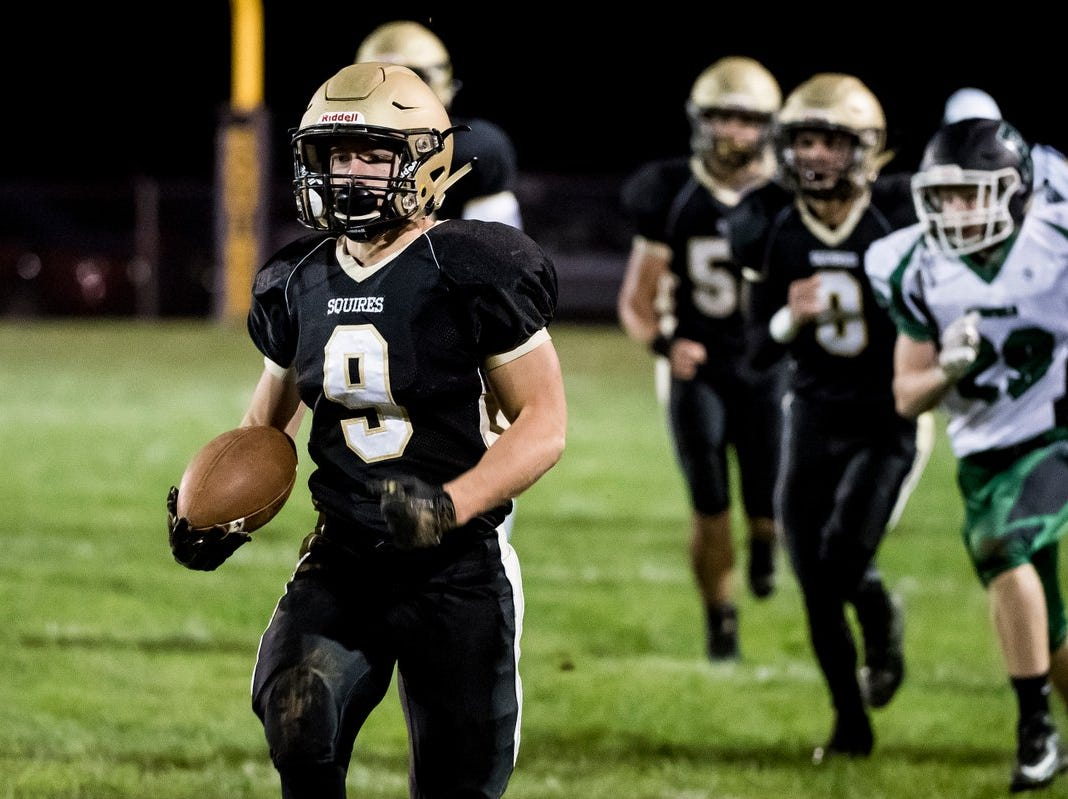 Delone Catholic's Logan Brown runs with the ball ahead of the pack Friday night against Fairfield.