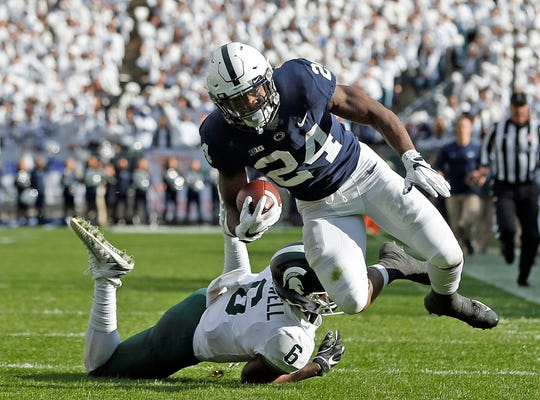 Penn State's Miles Sanders (24) is tripped by Michigan State's David Dowell (6) after a long run during the first half of an NCAA college football game in State College, Pa., Saturday, Oct. 13, 2018.