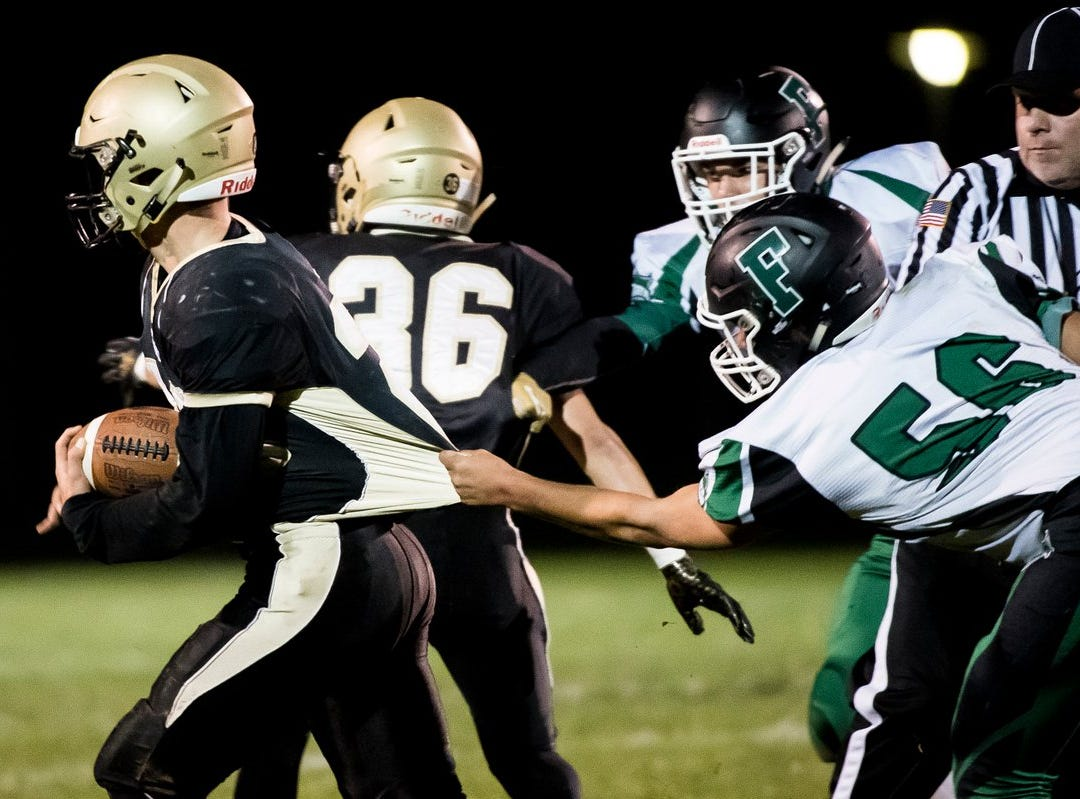 Fairfield's Zach Rutherford grabs a hold of a Delone Catholic offensive player on Friday night.