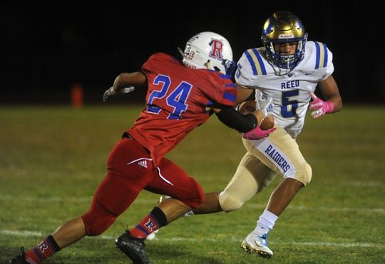 Reed's Brayden Mullen (5) tries to get past Reno's Anthony Hill during their football game at Reno on Oct. 12, 2018.
