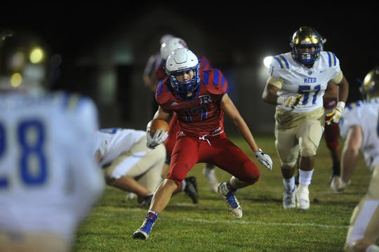 Reno's Ryan Gill (17) runs the ball while taking on Reed during their football game at Reno on Oct. 12, 2018.