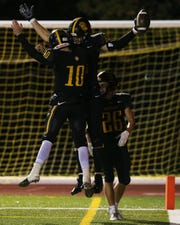 McQuaid's  Connor Zamiara and Hunter Walsh celebrate a touchdown against East. The pair connected on three TD passes in a 56-30 win.
