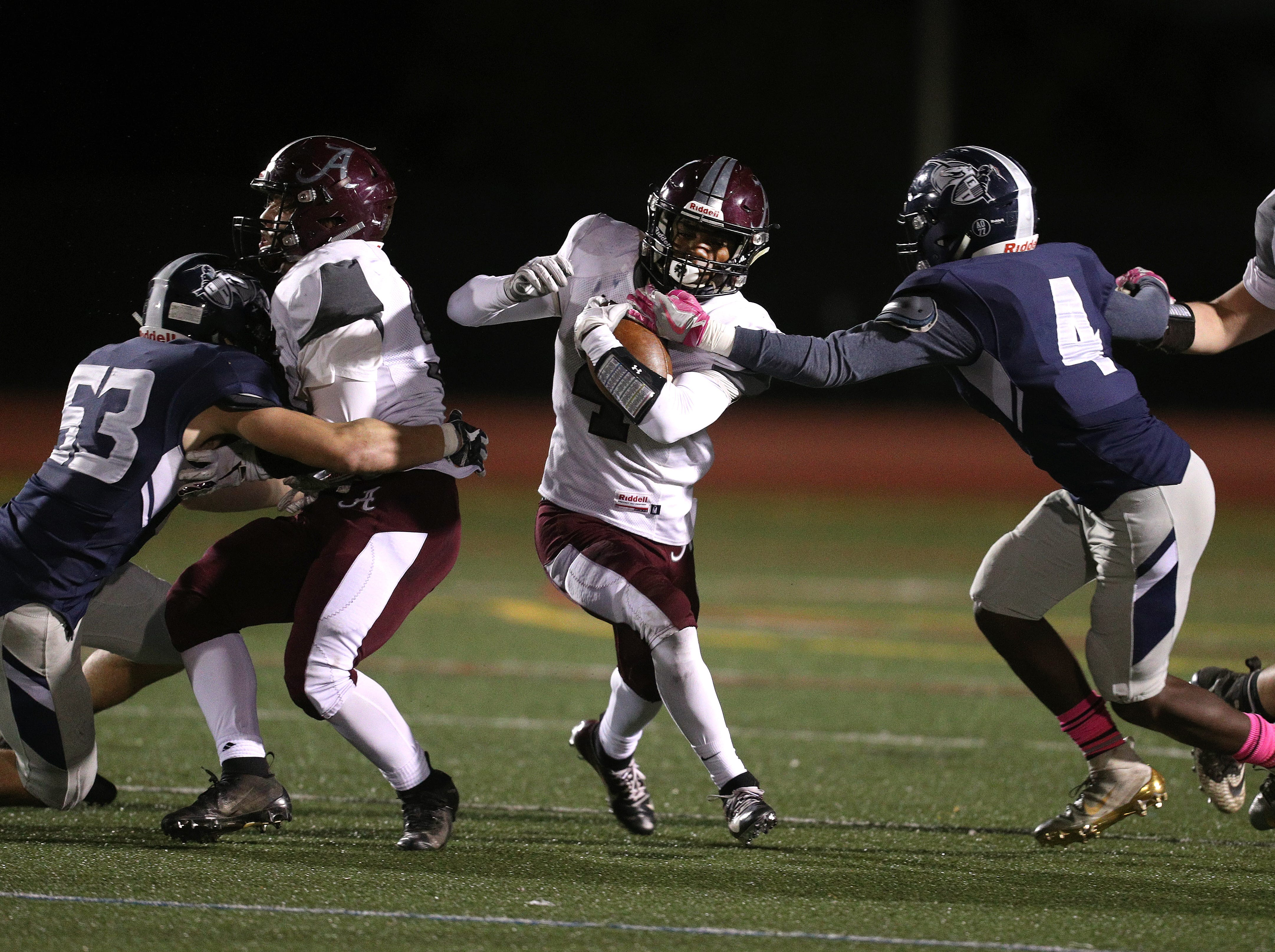 Arcadia running back K'myn Crumity tries to fight through a tackle by Eastridge's Koby Jones.