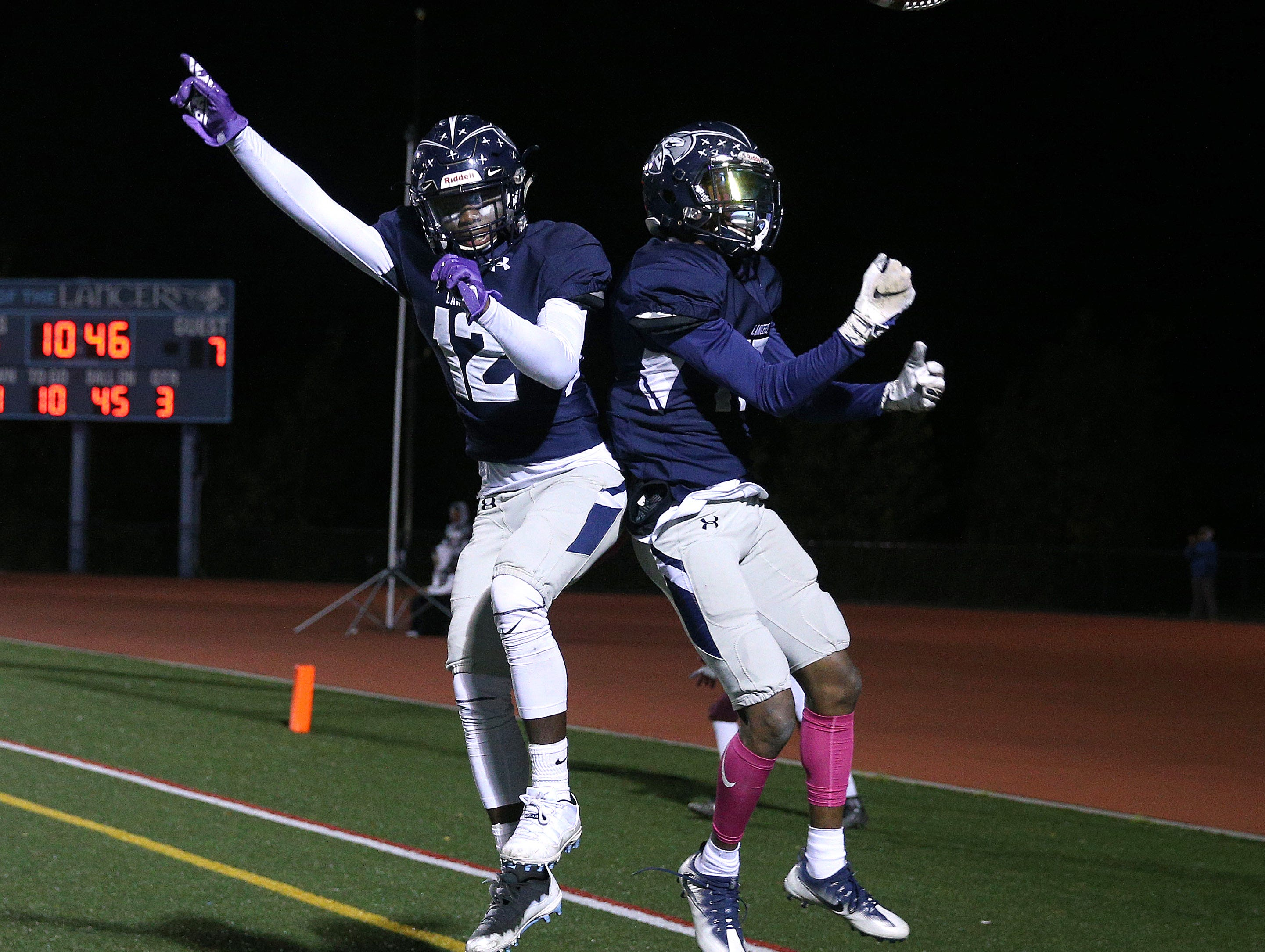 Eastridge's Jalen Rose Hannah (12) celebrates with Tony Arnold after Arnold's 45-yard touchdown reception early in the third quarter of the Lancers' win over Greece Arcadia.