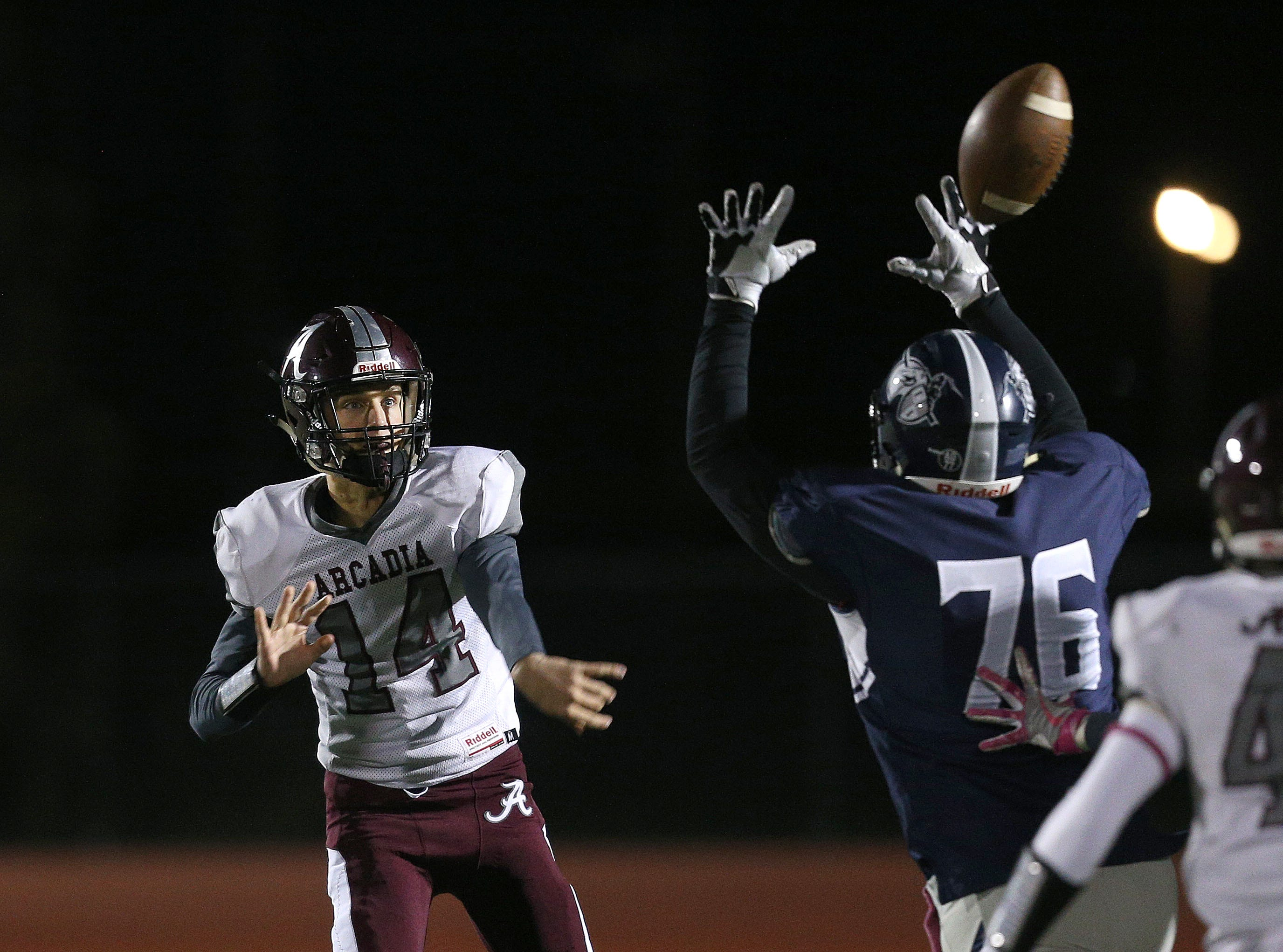 Arcadia quarterback Brian Shonitsky has this pass tipped at the line of scrimmage by Eastridge's Blerim Ilazi.