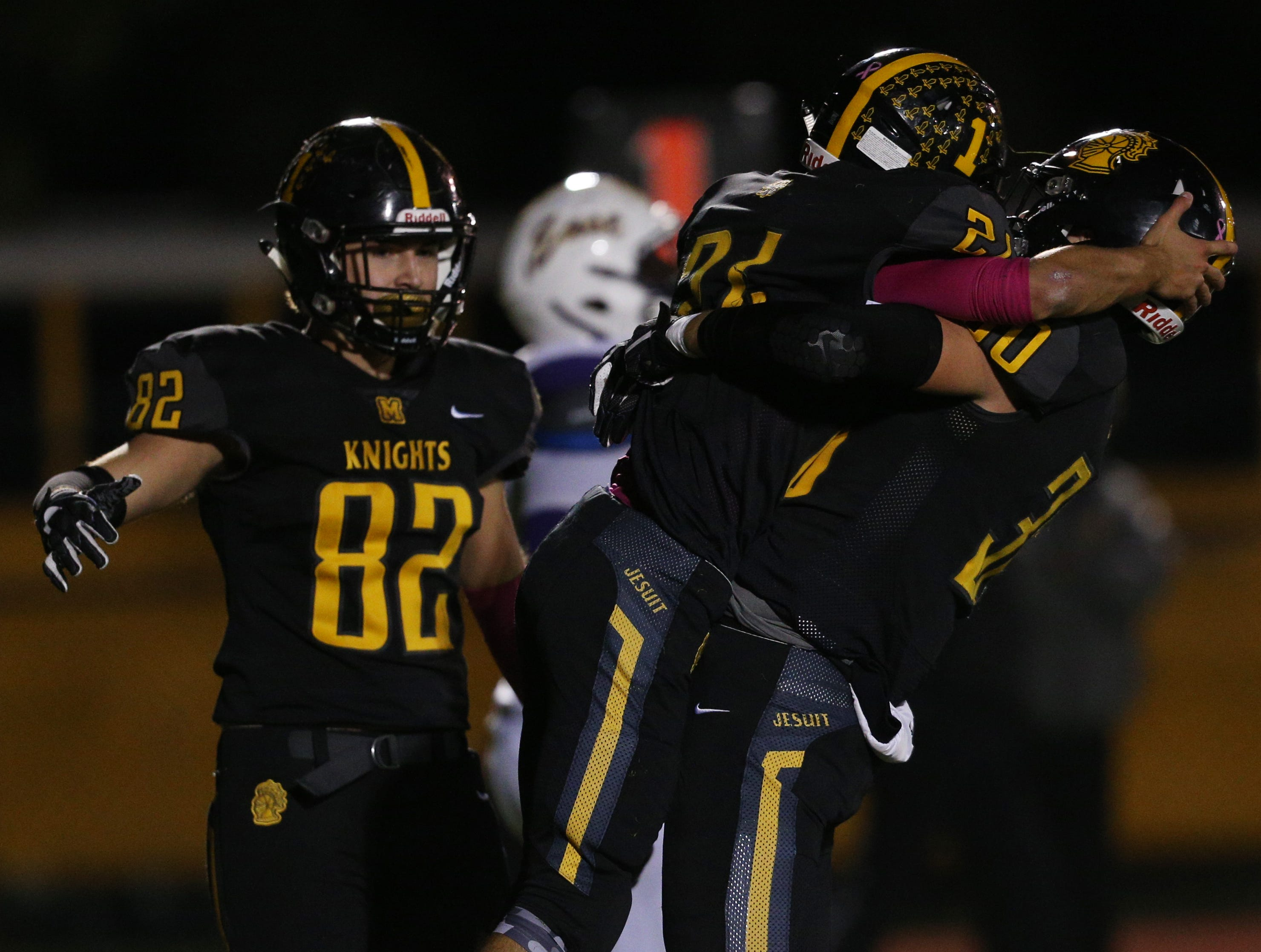 McQuaid's Mark Passero gets a hug after his touchdown against East.