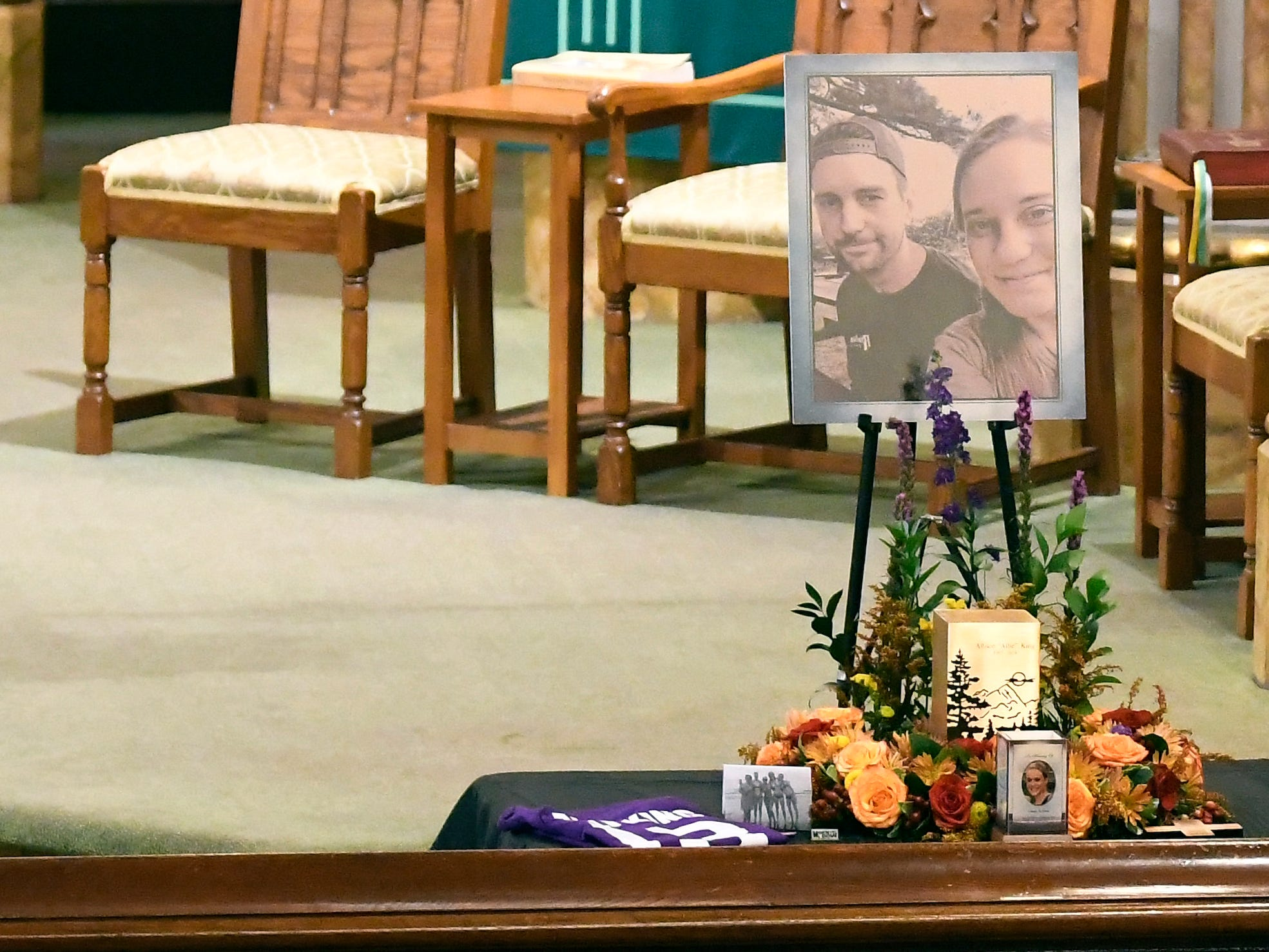 A urn with cremated ashes of Allison King is set in place as friends and family prepare for a funeral mass at St. Stanislaus Roman Catholic Church in Amsterdam, N.Y., for eight of the 20 people killed in last Saturday's fatal limousine crash in Schoharie, N.Y., Saturday, Oct. 13, 2018. (AP Photo/Hans Pennink)