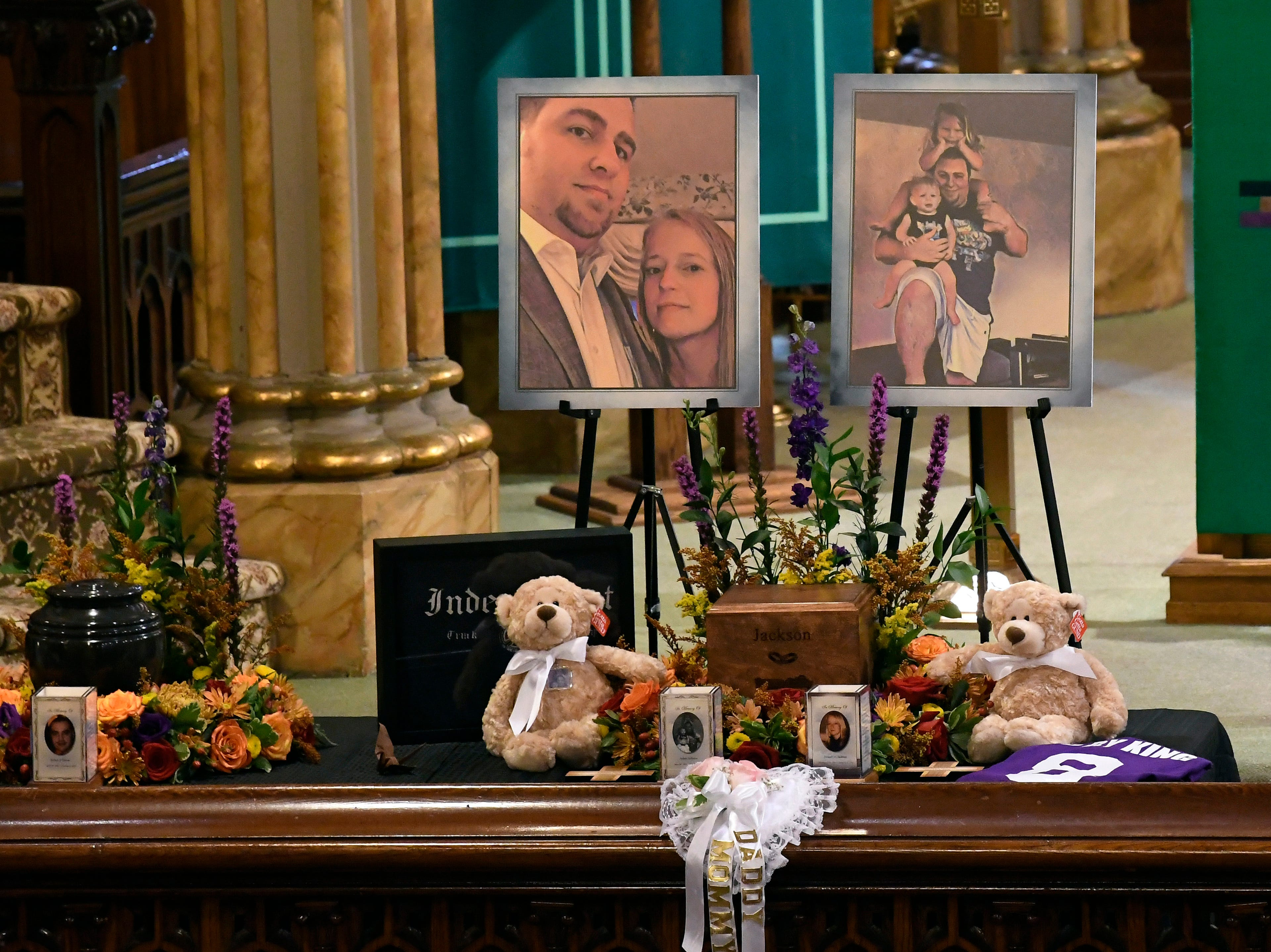 A unity urn with cremated ashes of Adam Jackson and Abigail Jackson is set in place as friends and family prepare for a funeral mass at St. Stanislaus Roman Catholic Church in Amsterdam, N.Y., for eight of the 20 people killed in last Saturday's fatal limousine crash in Schoharie, N.Y., Saturday, Oct. 13, 2018. (AP Photo/Hans Pennink)