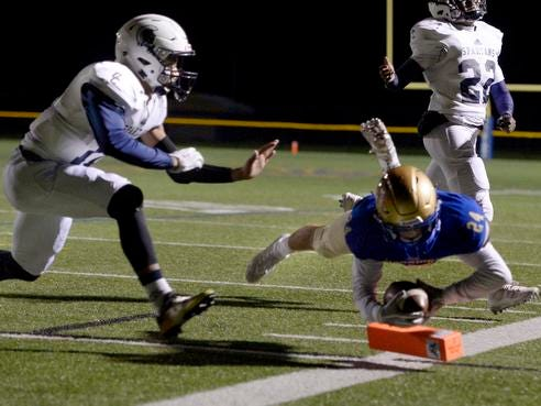 Webster Schroeder's Luke Lupisella dives for the pylon in front of Gates Chili's Mair Morrison to score the Warriors' second touchdown against Gates Chili during Friday night's regular-season finale at Schroeder.