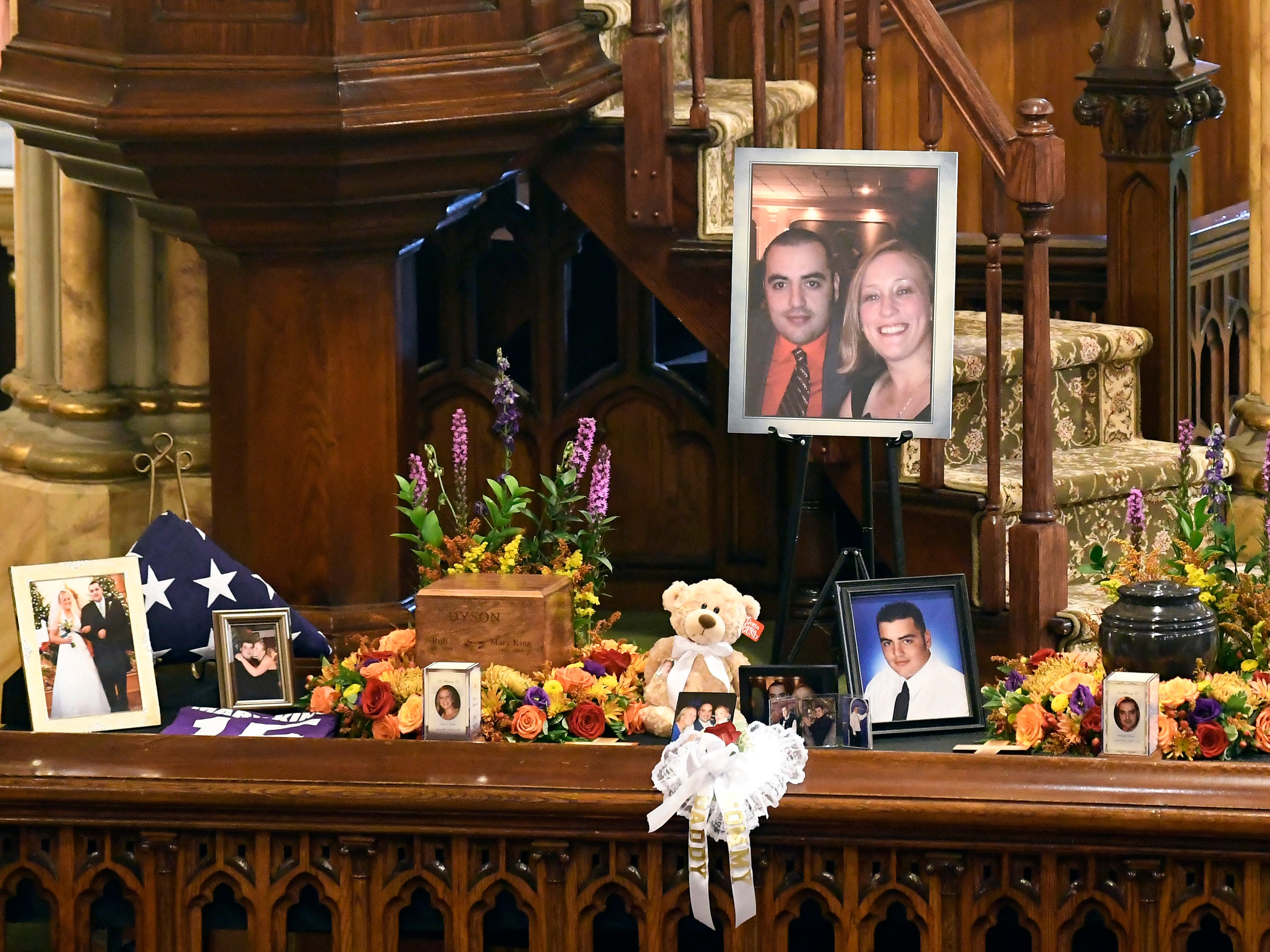 A unity urn with cremated ashes of Robert Joseph Dyson and Mary E. Dyson is set in place as friends and family prepare for a funeral mass at St. Stanislaus Roman Catholic Church in Amsterdam, N.Y., for eight of the 20 people killed in last Saturday's fatal limousine crash in Schoharie, N.Y., Saturday, Oct. 13, 2018. (AP Photo/Hans Pennink)