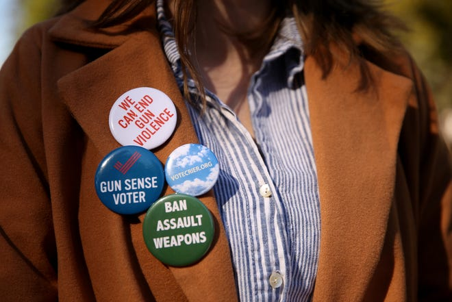 Alyssa Thompson, 17, a South Salem High School graduate, wears buttons on her lapel during an event to register voters before the Tuesday deadline outside the Oregon State Capitol in Salem on Saturday, Oct. 13, 2018.
