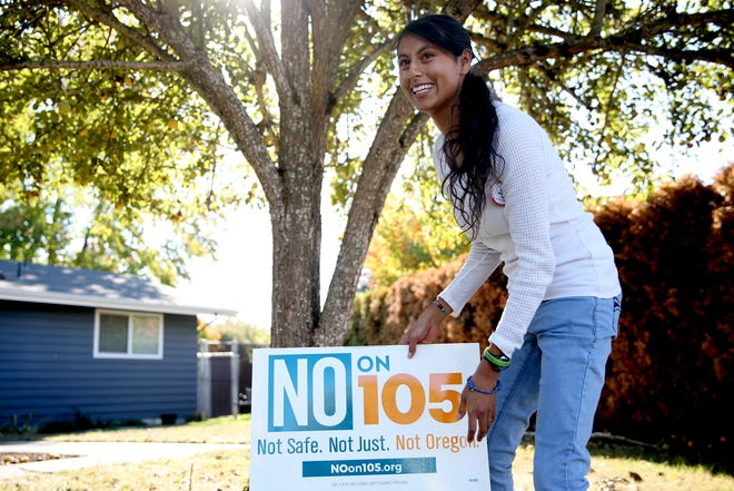 Diana Alvarez Ramirez, a Spanish teacher at Sprague High School and a DACA recipient, sets up a sign in a supporter's yard as she canvasses door-to-door with Oregonians United Against Profiling and No on Measure 105 in Northeast Salem on Saturday, Oct. 13, 2018. Measure 105 would repeal Oregon's sanctuary state law.