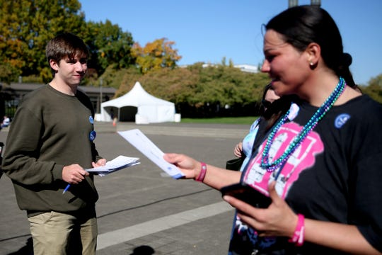Wylie Thompson, left, a Sprague High School senior, hands out a voter registration form to Dusty Graham, of Salem, in an effort to register voters before the Tuesday deadline outside the Oregon State Capitol in Salem on Saturday, Oct. 13, 2018.