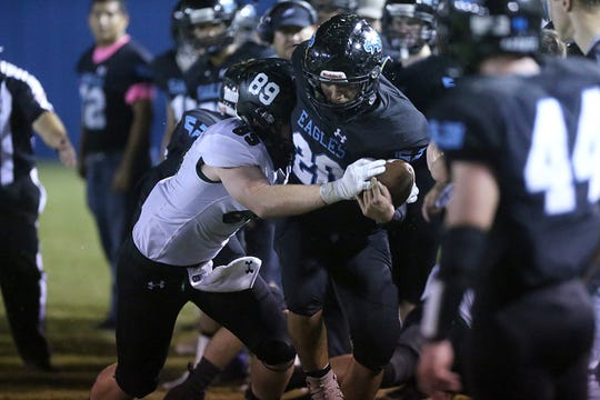 TLCA's Eddie Carranco (20) is pushed into the sidelines Friday, Oct. 10, 2018, by Grape Creek's Dalton Penaluna.
