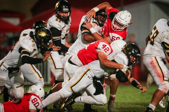 Miles' Christian Gutierrez (68) tries to fight through a block against Menard on Friday, Oct. 12, 2018, in Miles.