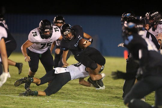 TLCA's Sterling Harding (#1) gets brought down by his legs Friday, Oct. 10, 2018 by Grape Creek's Jorge Rodriguez and help from his teammate Hagen Delagarza (#75).