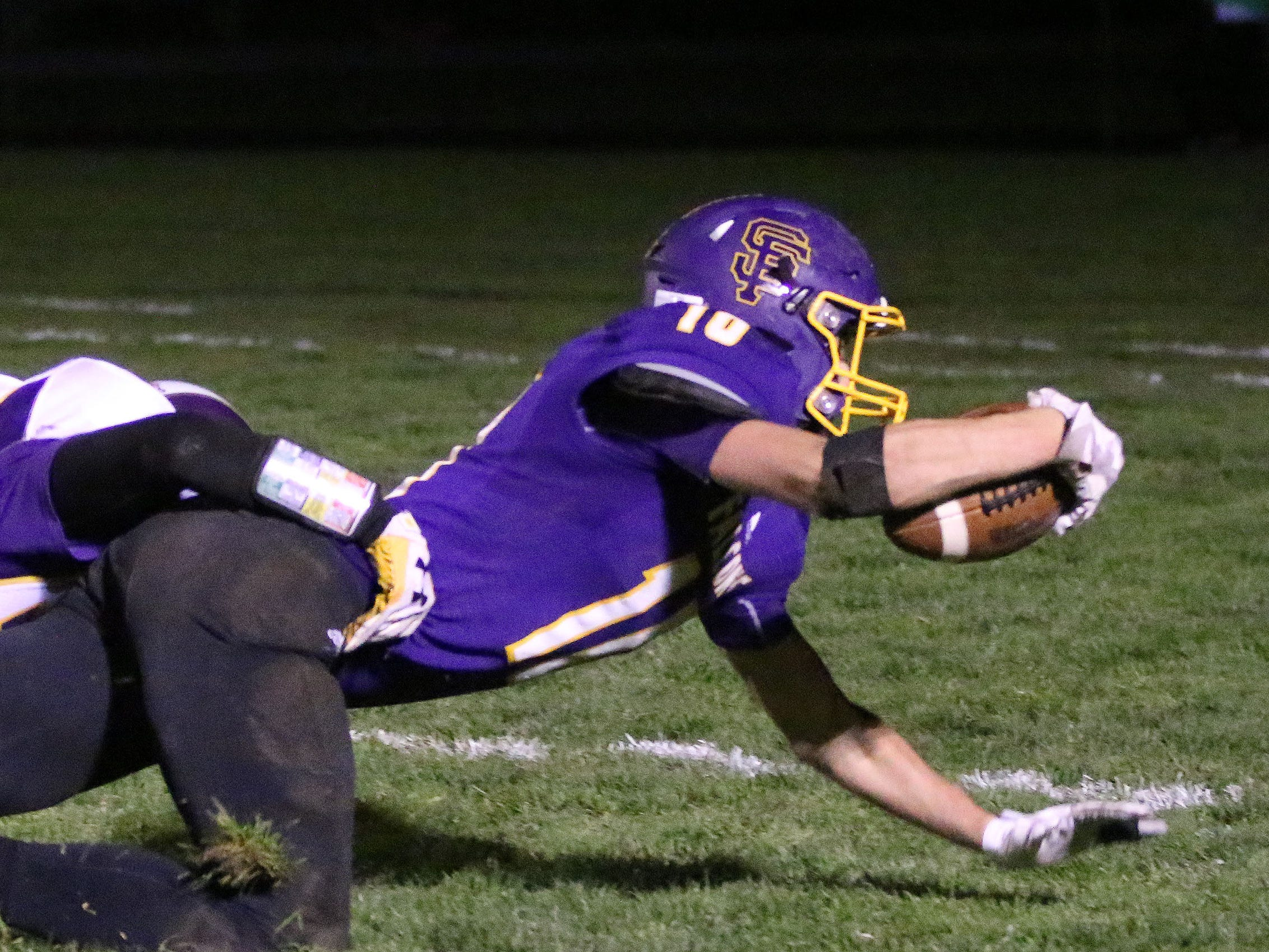 Sheboygan Falls' Justin Tenpas (10) stretches to gain yardage by Two River's Logan Perry (27), Friday, October 12, 2018, in Sheboygan Falls, Wis.