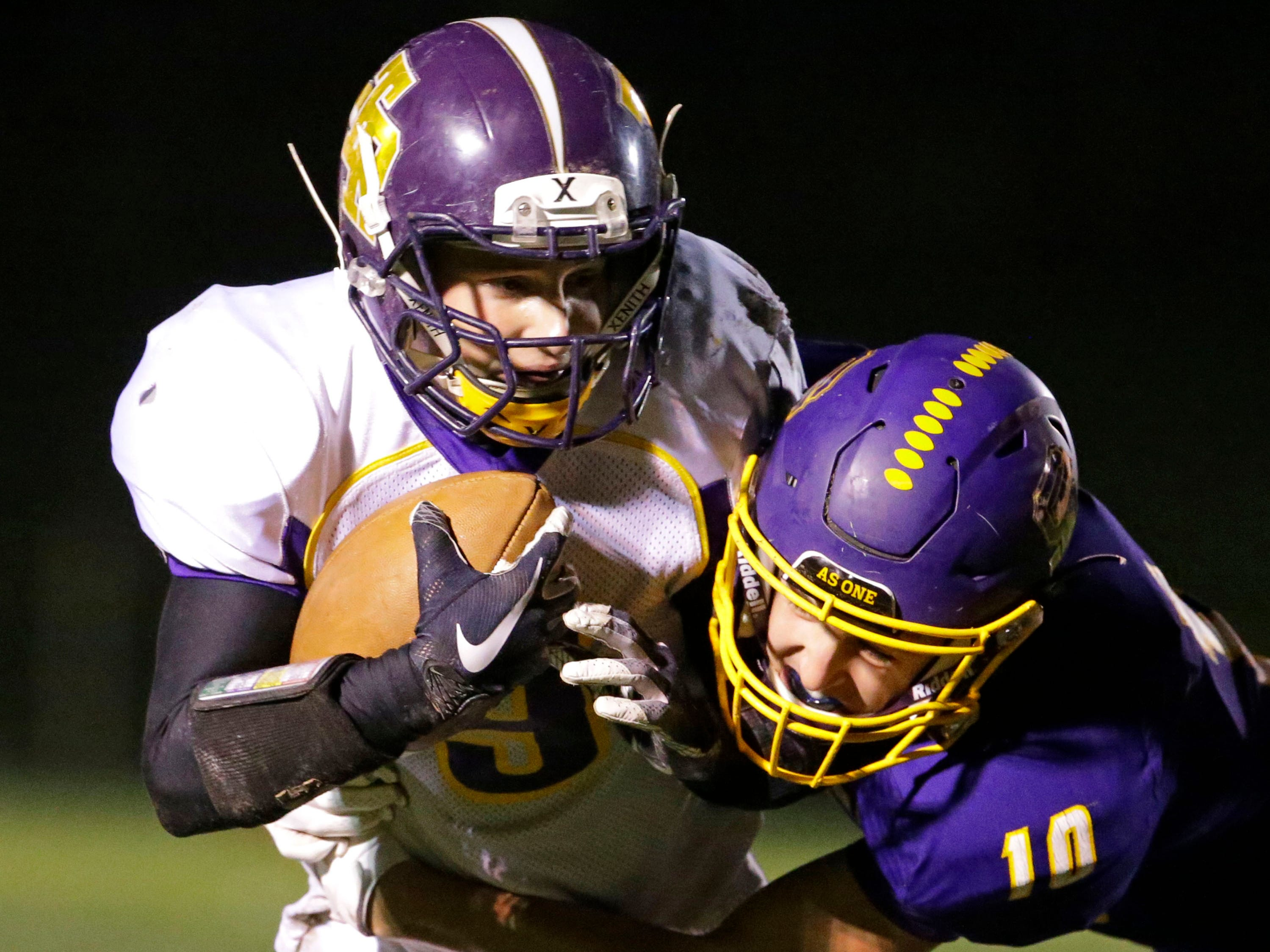 Two River's Carson Koch (9) is gripped by Sheboygan Falls' Justin Tenpas (10), Friday, October 12, 2018, in Sheboygan Falls, Wis.