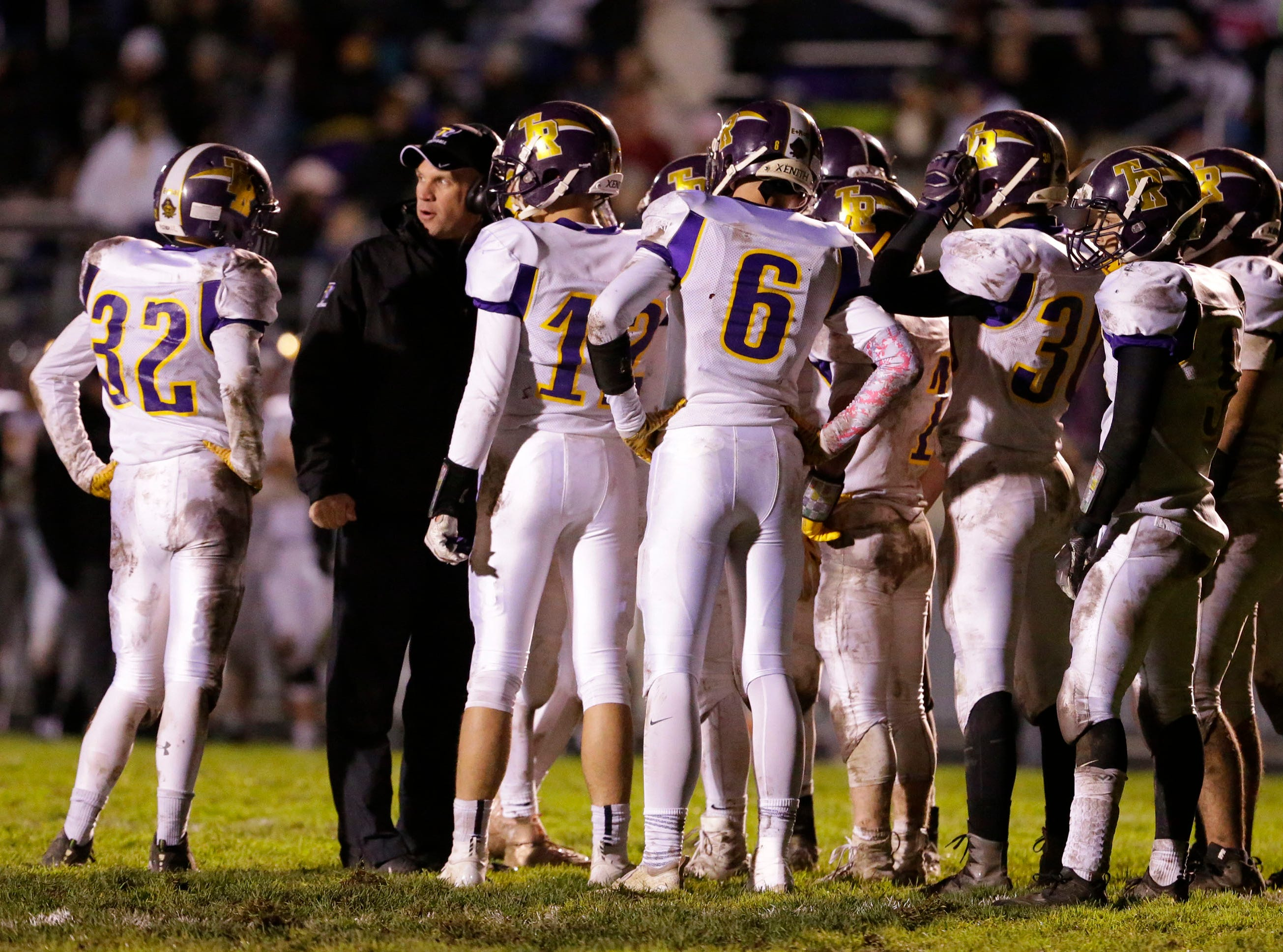 Two Rivers' coach Kevin Shillcox, left, talks strategy with his team against Sheboygan Falls, Friday, October 12, 2018, in Sheboygan Falls, Wis.