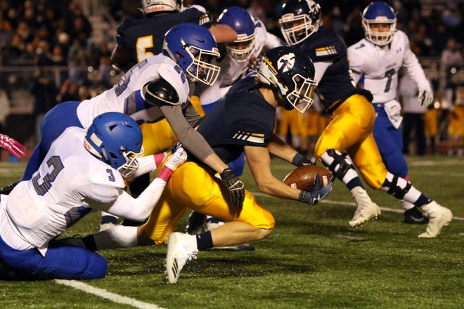 Carter Slykhuis of Tea Area stretches for extra yardage as Clay Vinson (3) and Mitchell Walker of Sioux Falls Christian make the tackle during Friday's game in Tea.