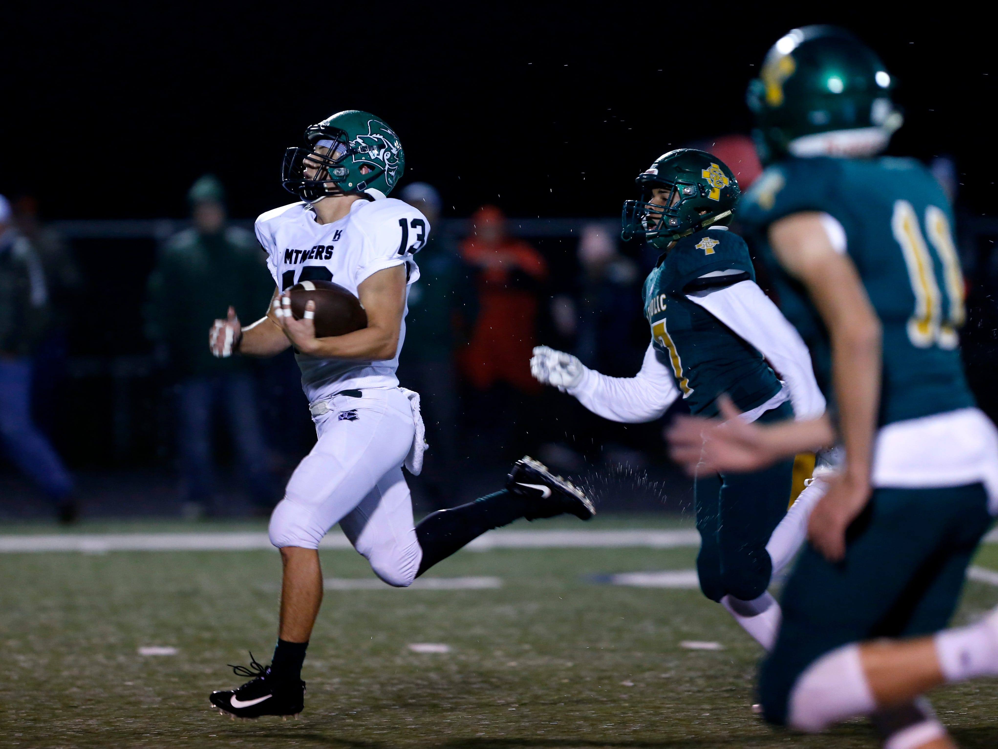 Mt. Vernons Carson Bow carries the ball downfield with Springfield Catholics Peyton James in pursuit during a game at Catholic on Friday, Oct. 12, 2018.