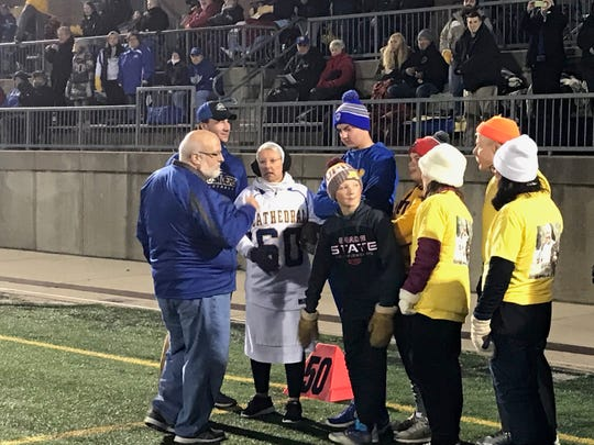 Sister Mary Jo Sobieck (60) plans out her ceremonial pass play before Cathedral High School's homecoming game Friday at Husky Stadium. Sobieck, who teaches at Marian Catholic High School in Illinois, gained fame for her ceremonial first pitch before a Chicago White Sox game.