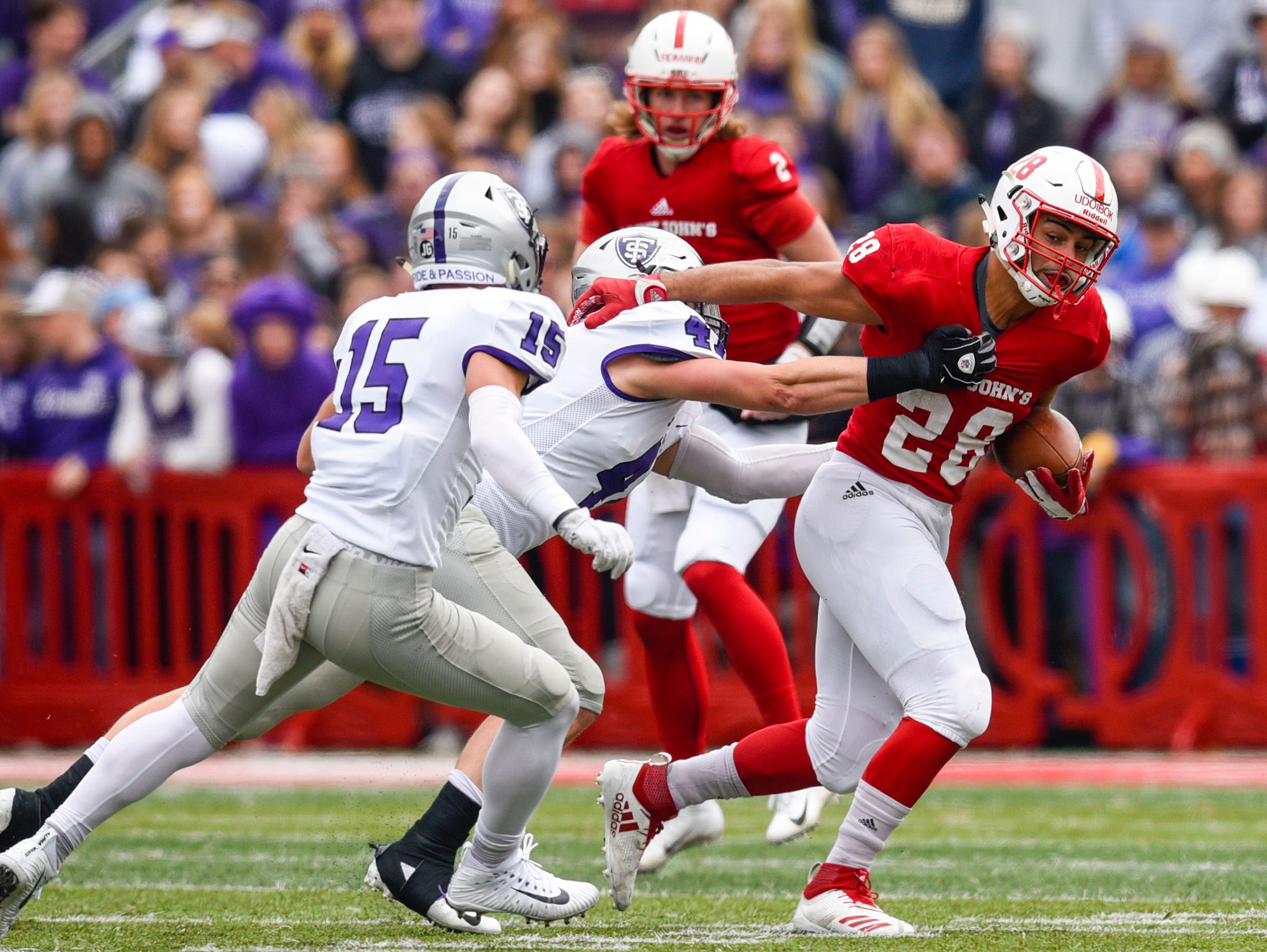 St. John's running back Kenneth Udoibok tries to push off a St. Thomas defender on a run during the first half Saturday, Oct. 13, in Collegeville.