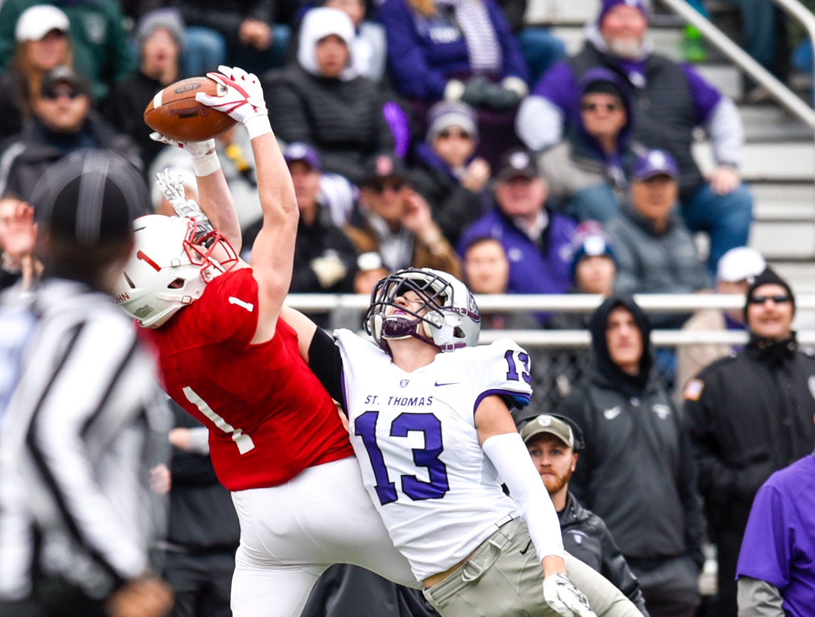 St. John's wide receiver Joey Eckhoff grabs a pass over Thomas' Sam Gerrety during the first half Saturday, Oct. 13, in Collegeville.