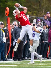 St. John's wide receiver Joey Eckhoff pulls in a pass over St. Thomas' Chris Fondakowski for a first down during the first half Saturday, Oct. 13, in Collegeville.
