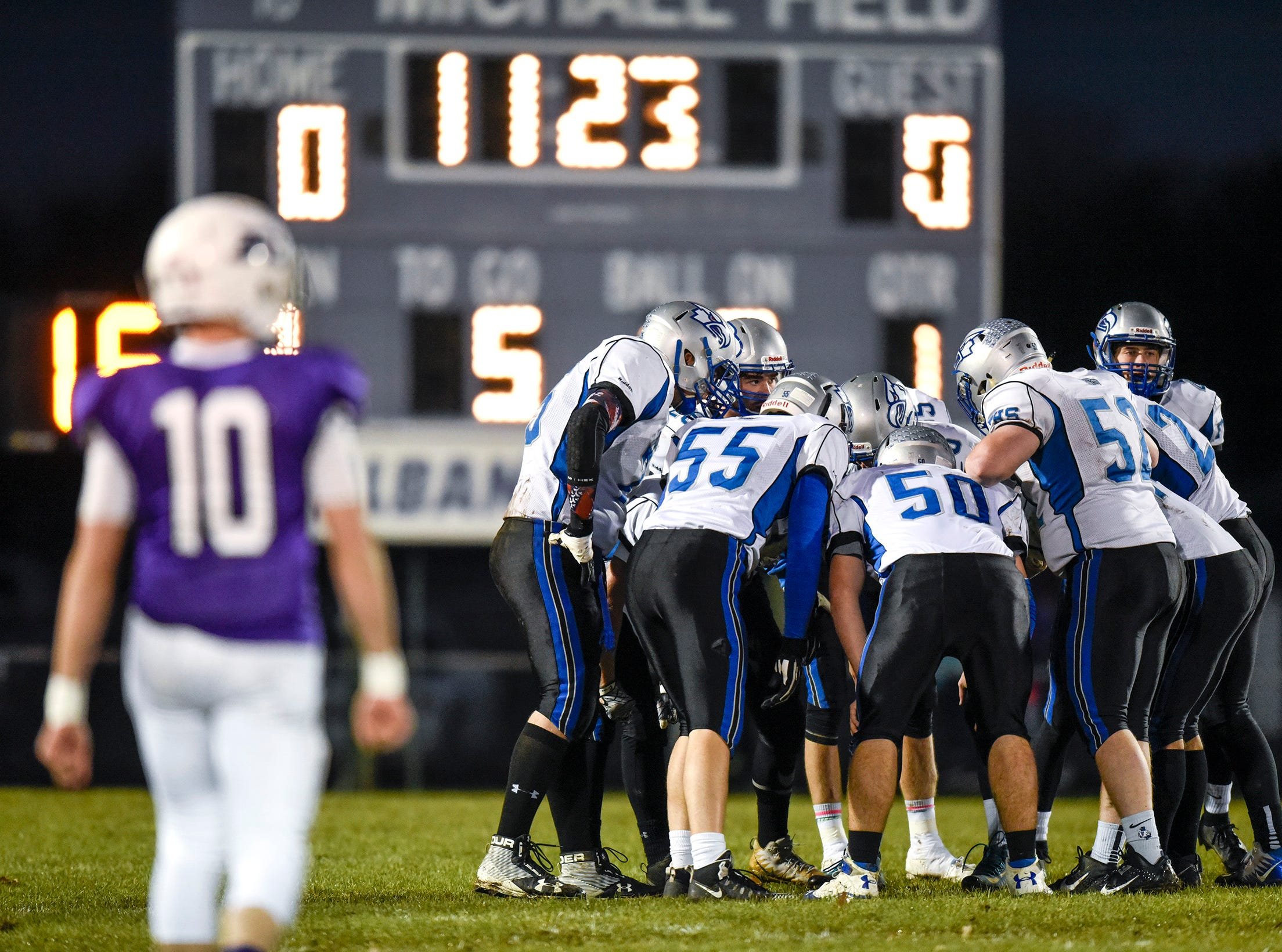 Foley players call the play in the huddle during the first half Friday, Oct. 12, in Albany.