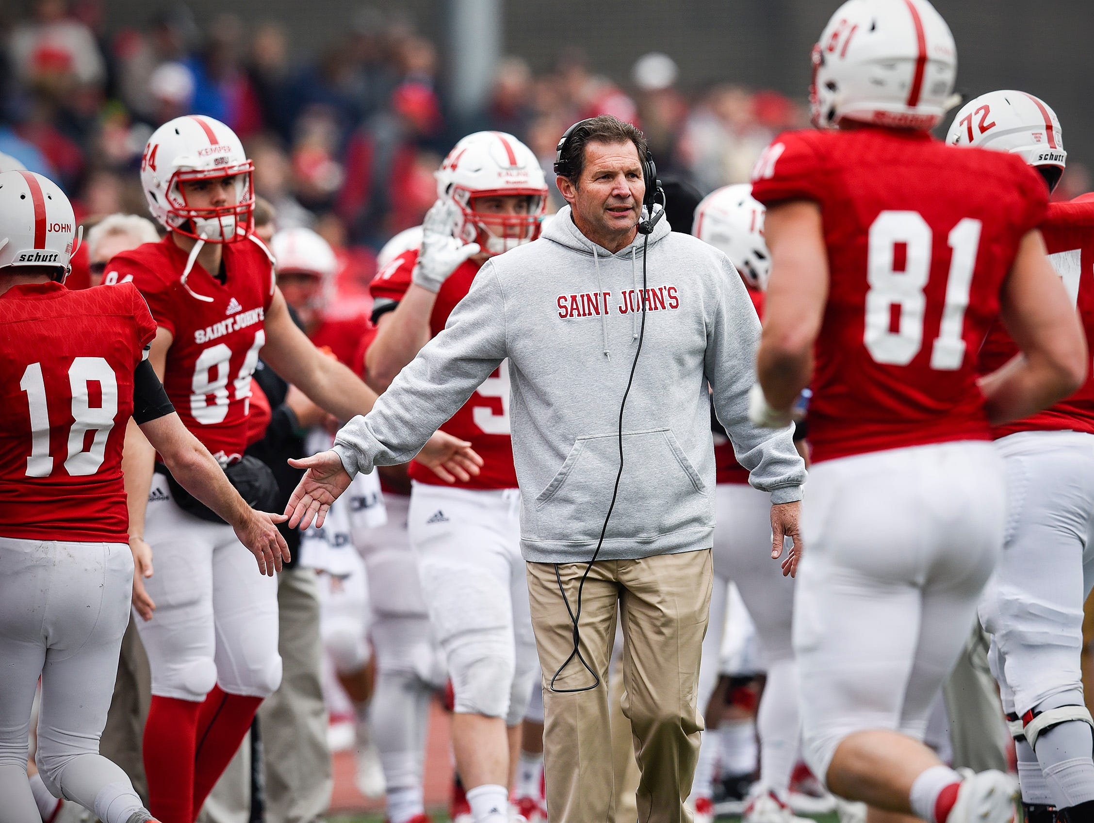 St. John's head coach Gary Fasching celebrates a touchdown with players as they come off the field against St. Thomas during the first half Saturday, Oct. 13, in Collegeville.