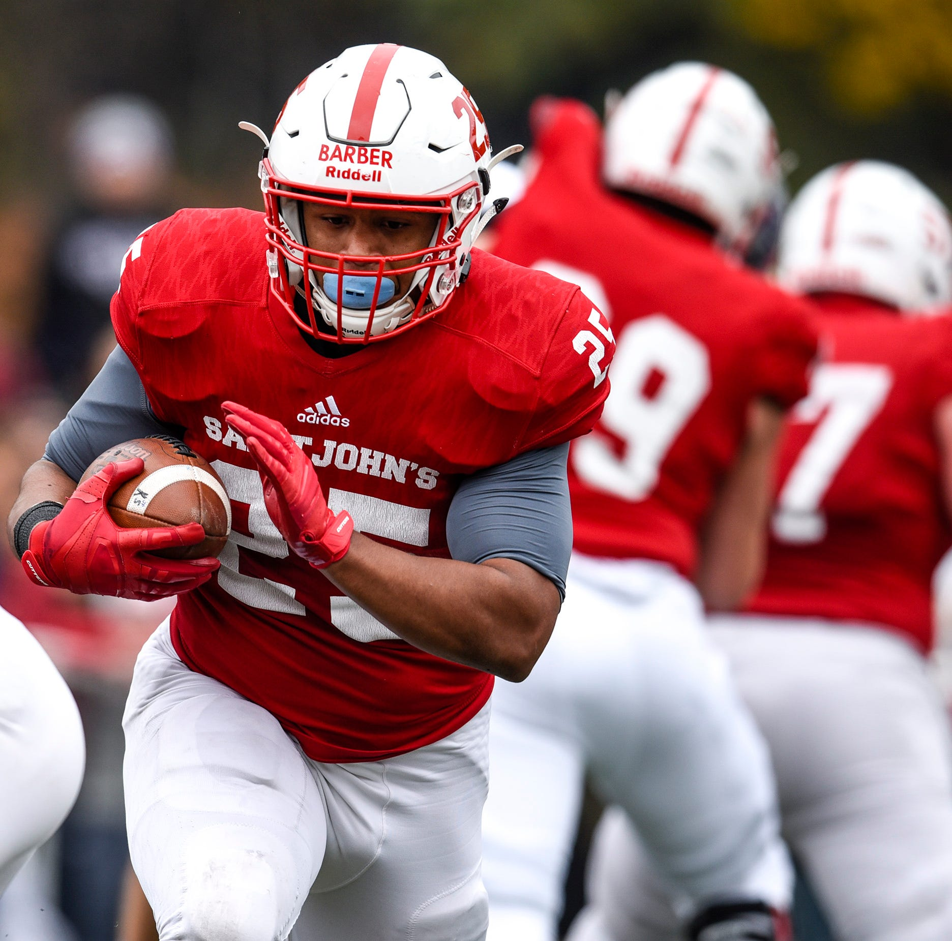 St. John's running back Kai Barber breaks through the St. Thomas defense for a gain during the first half Saturday, Oct. 13, in Collegeville.