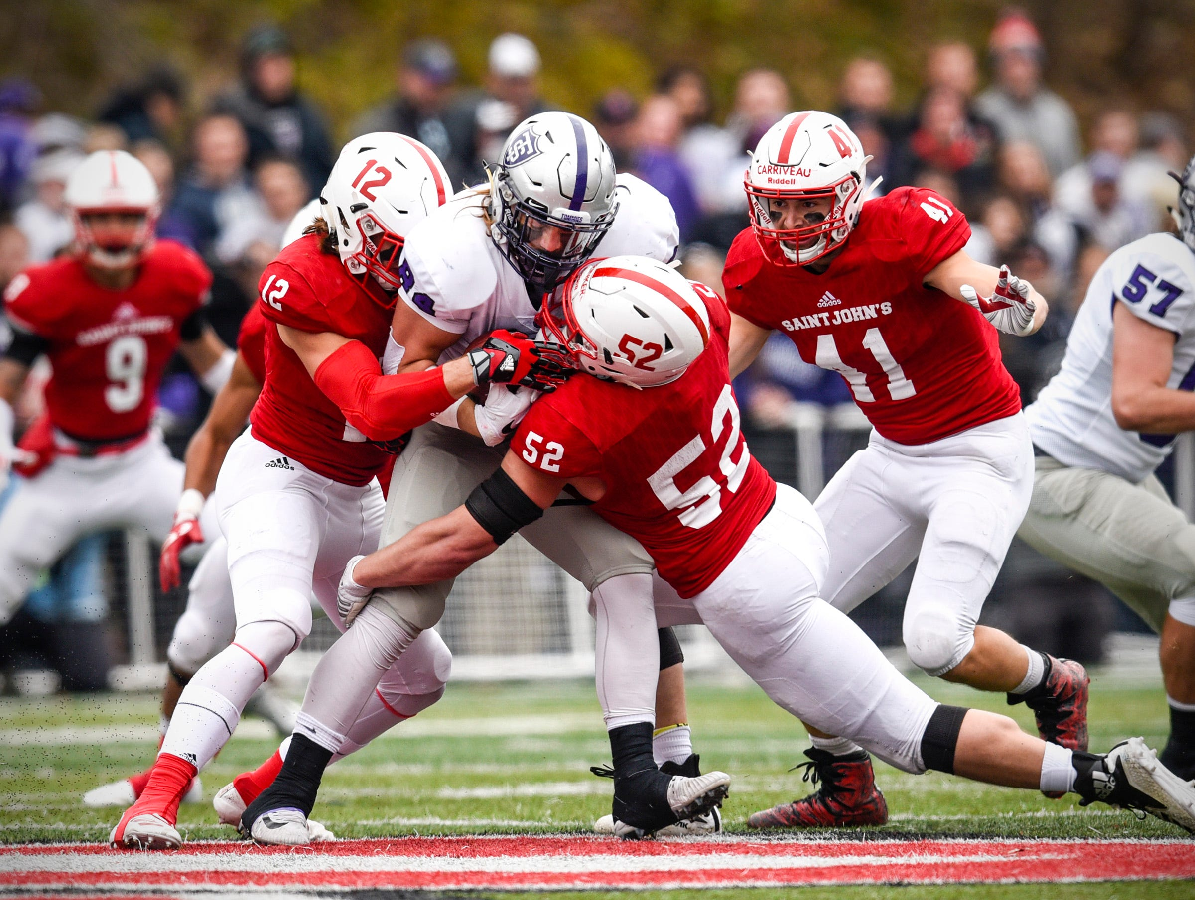 St. John's Ryan LaCasse and Nathan Brinker bring down St. Thomas full back Jack Foley during the first half Saturday, Oct. 13, in Collegeville.