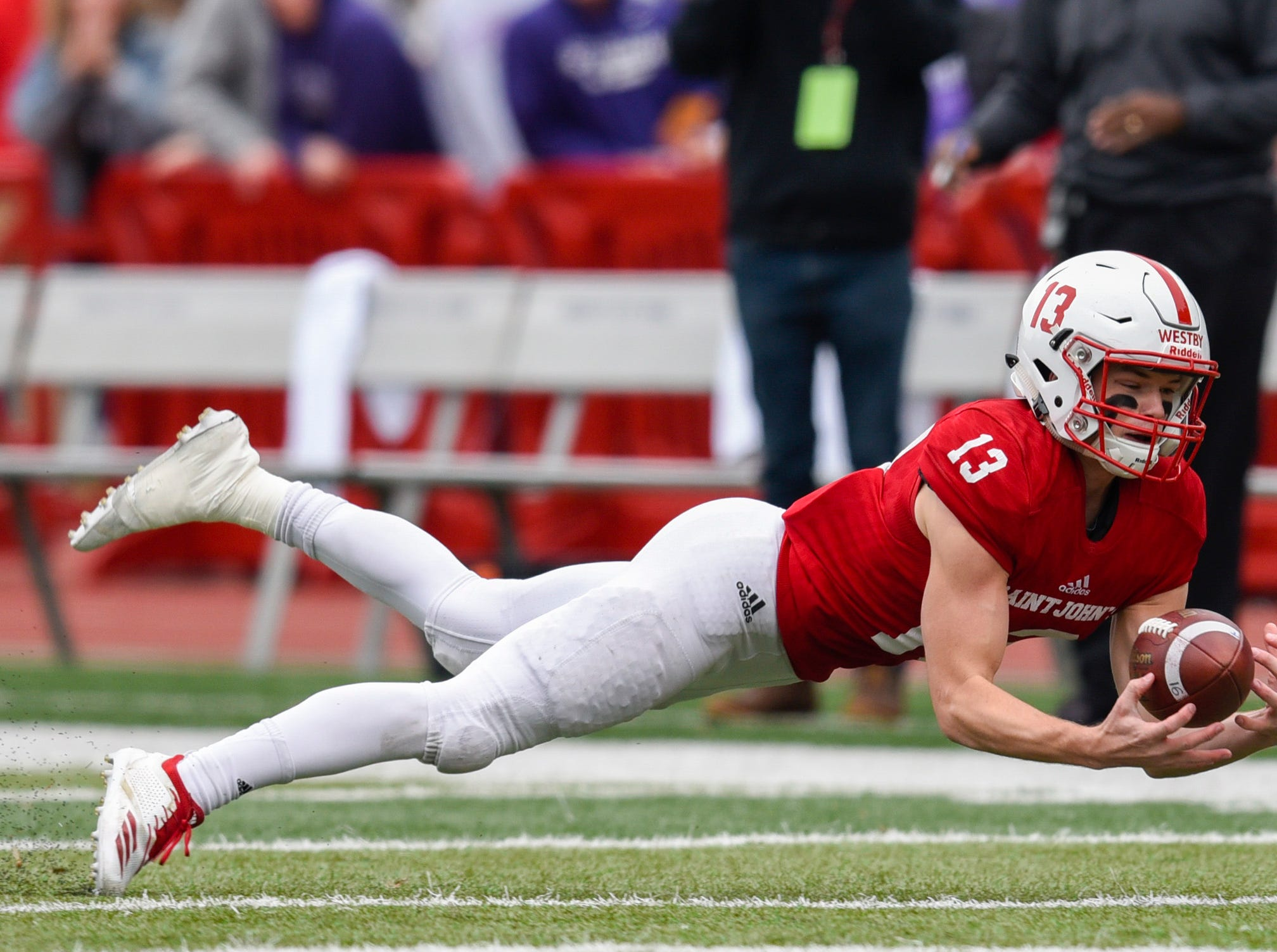 St. John's defensive corner Sam Westby dives to make an interception against St. Thomas during the first half Saturday, Oct. 13, in Collegeville.