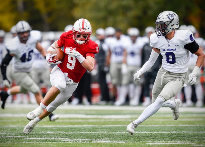 St. John's wide receiver Will Gillach gains yardage against the St. Thomas in the Johnnies' 40-20 win last October. The rivalry between the schools is considered one of the biggest in college football.