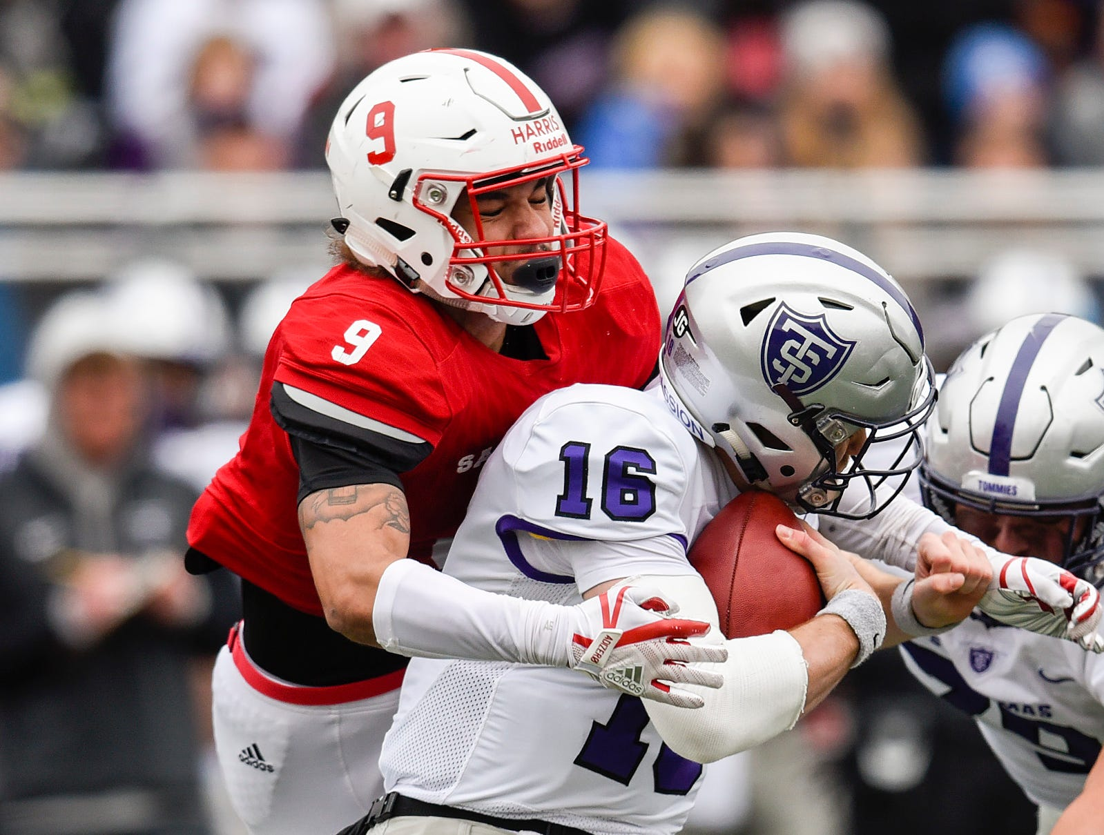 St. John's Chris Harris sacks St. Thomas quarterback Jacques Perra for a loss during the first half Saturday, Oct. 13, in Collegeville.
